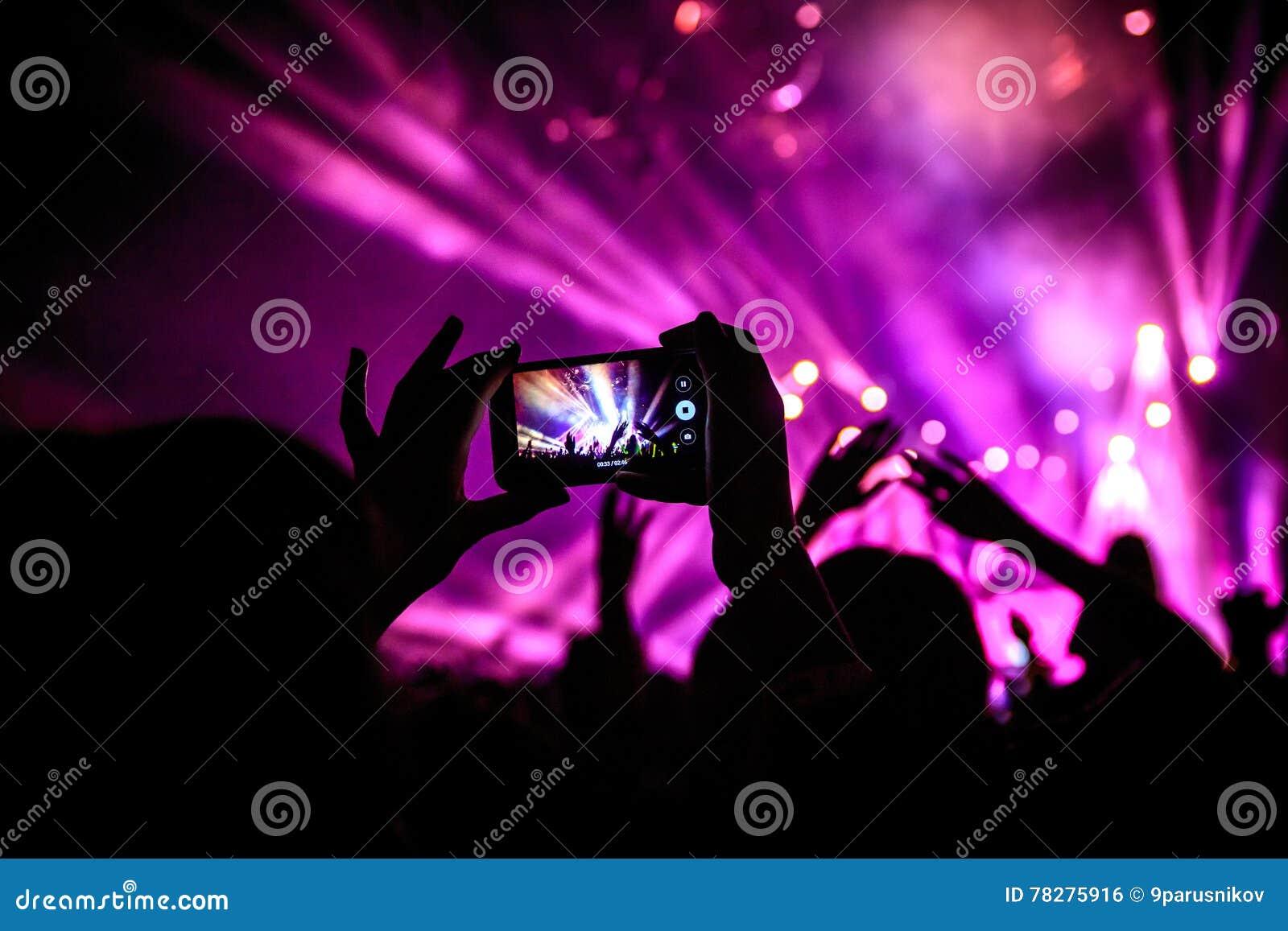 La main avec un smartphone enregistre le festival de musique en direct, prenant la photo de l étape de concert
