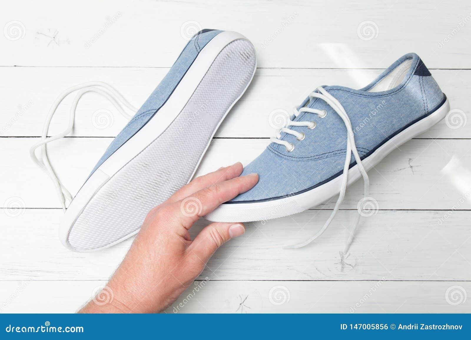 La main d homme choisit des espadrilles de blues-jean sur un fond en bois blanc