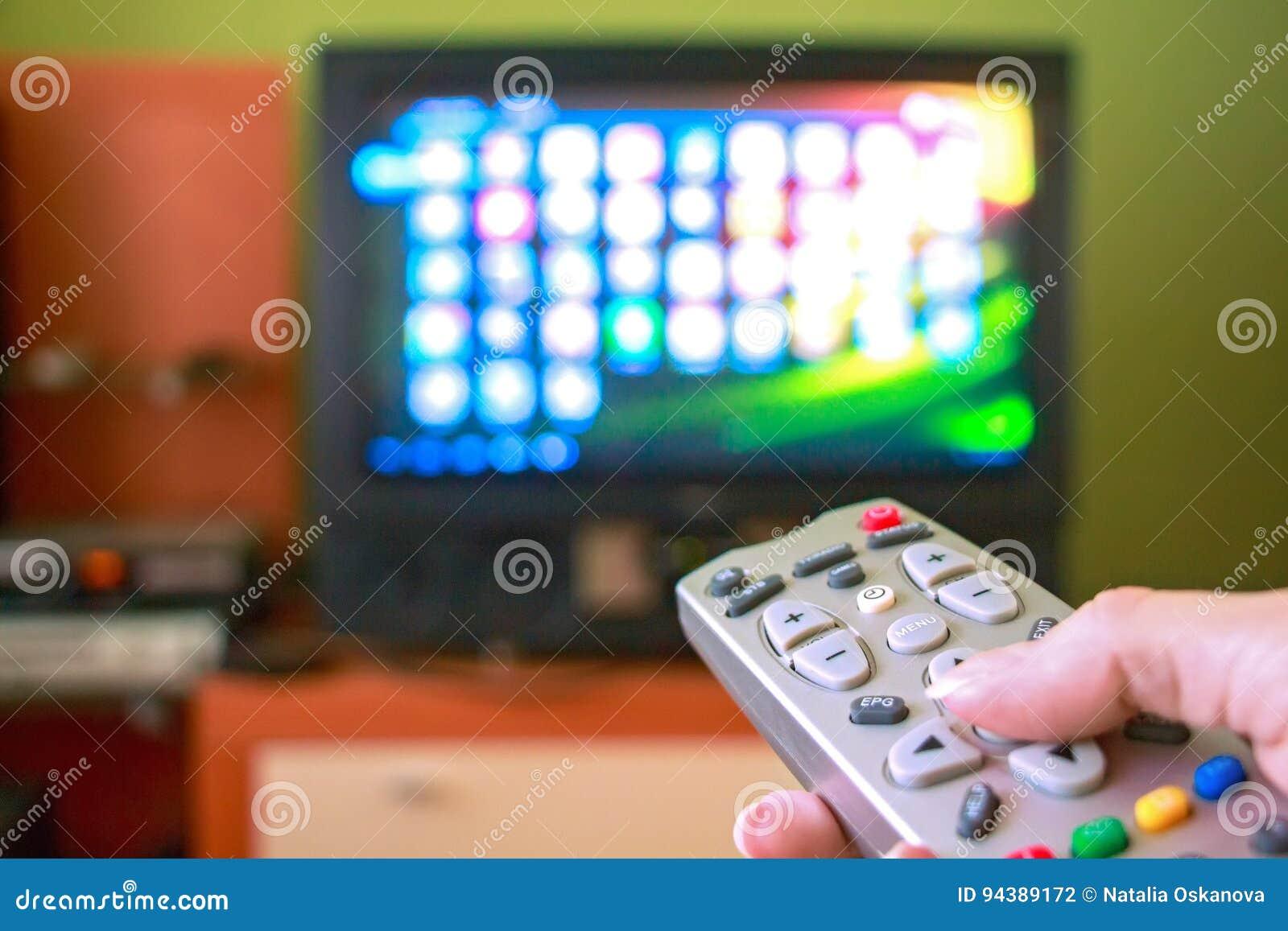 La main de femme tient la TV à télécommande