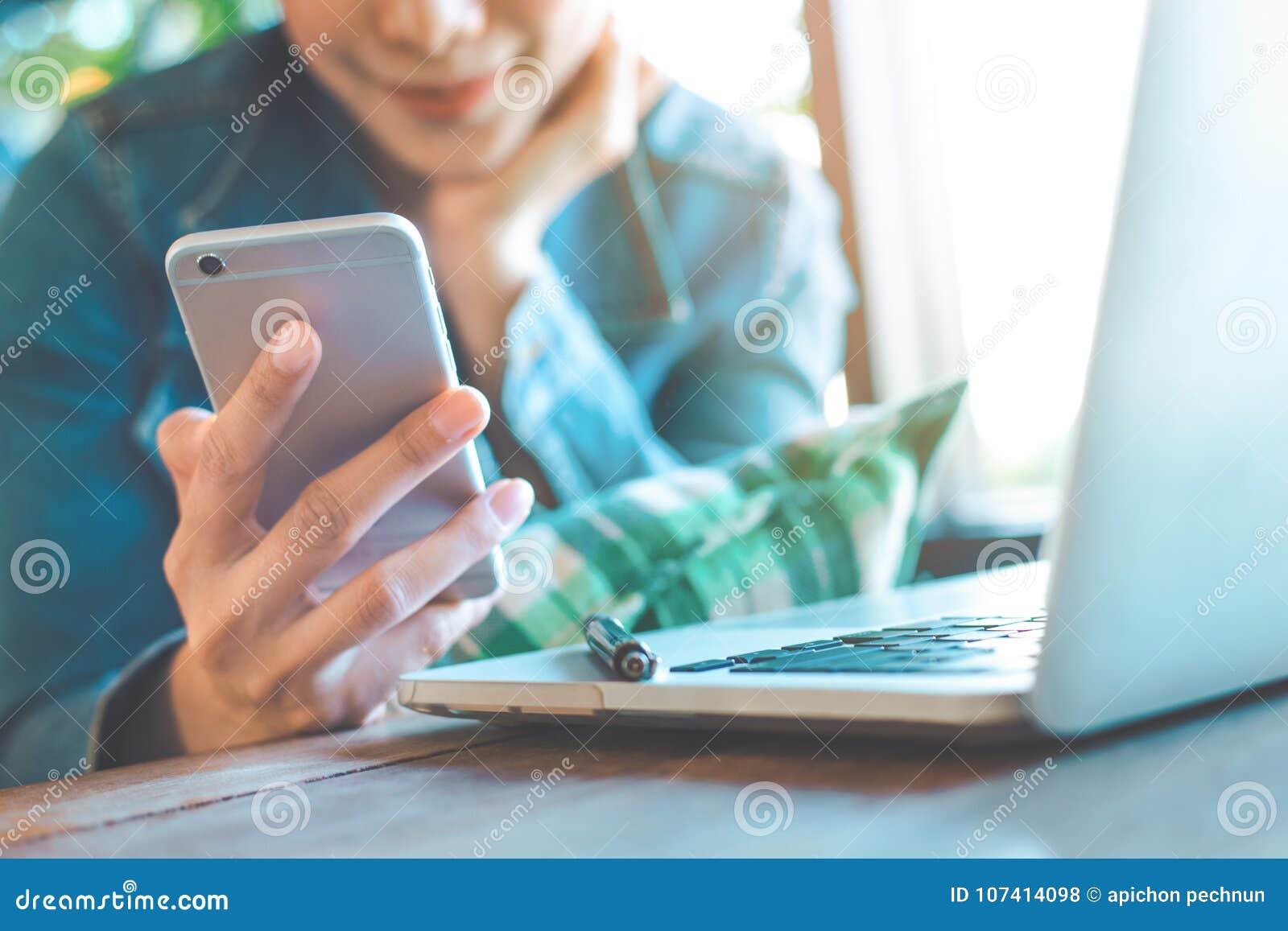 La main de femme utilise un téléphone portable et fonctionne dans un ordinateur portable aux bureaux