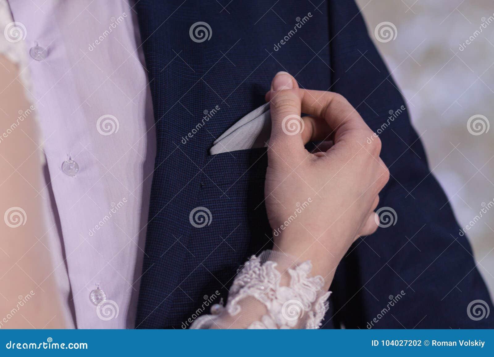 La main de la fille corrige ou retire un mouchoir sur la poche de poitrine de la veste bleue du ` s d homme Plan rapproché