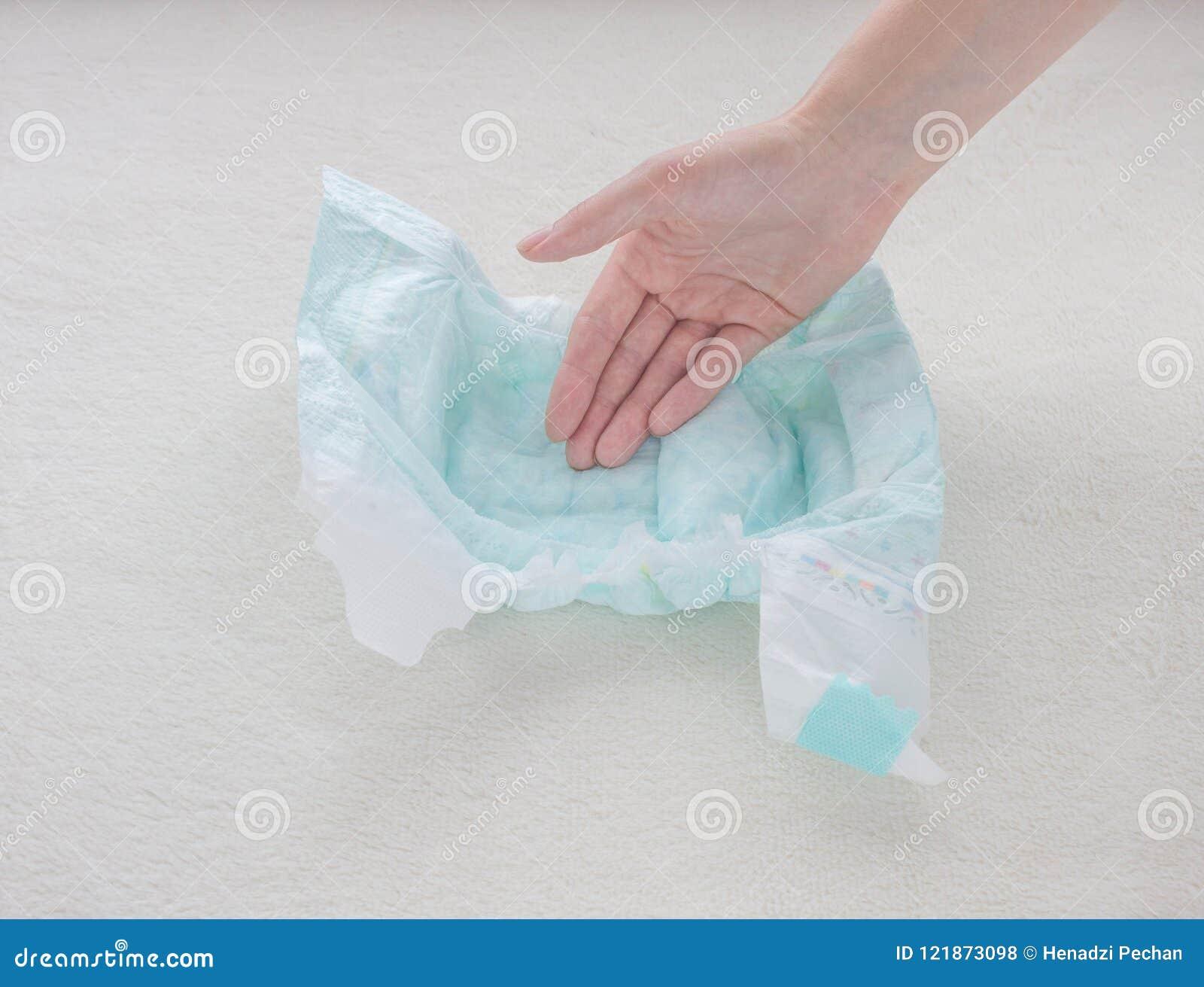 La main de fille touche l absorptivité d humidité d une couche-culotte de bébé, plan rapproché