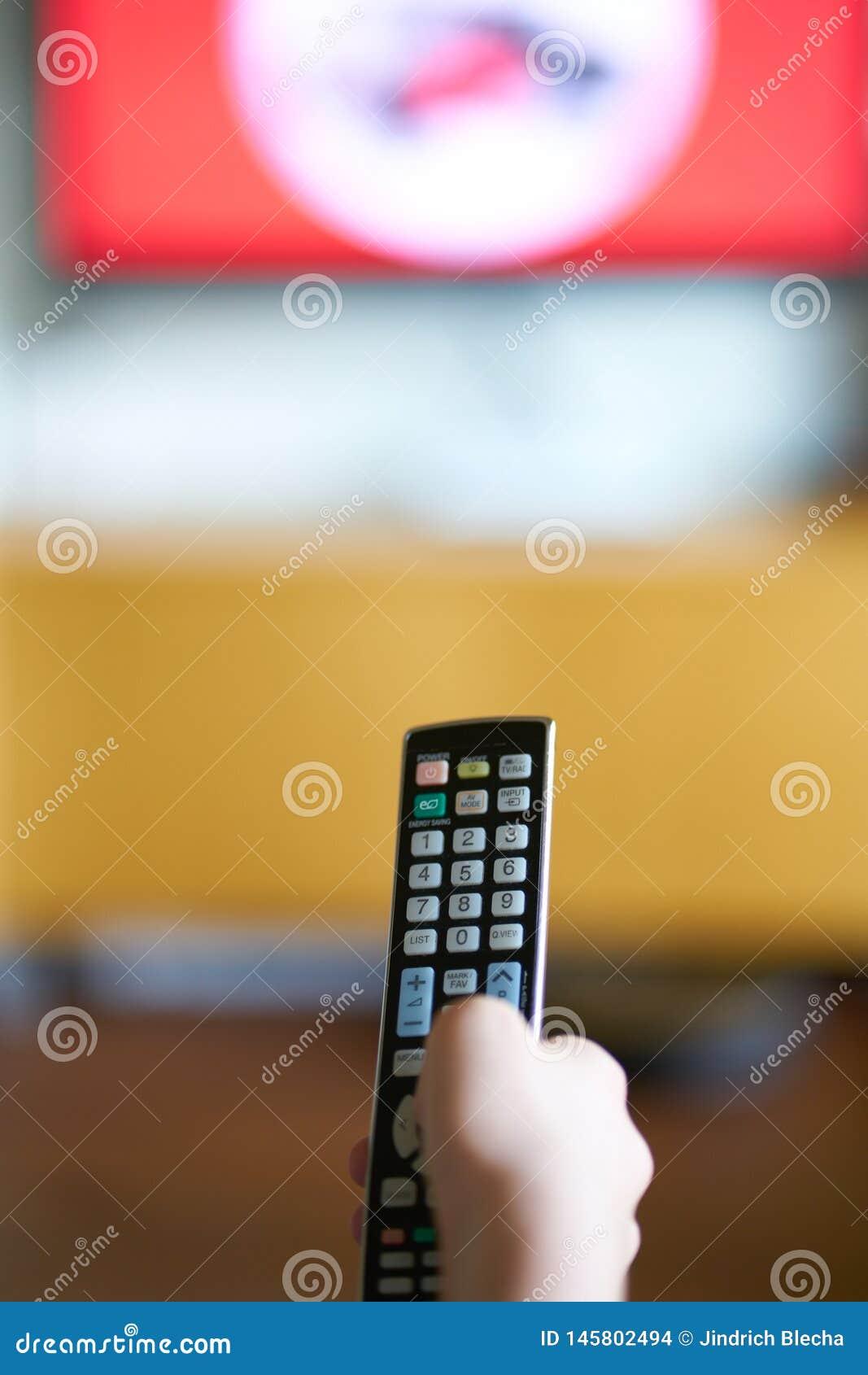 La main de Kidtenant un contrôleur à distance de TV
