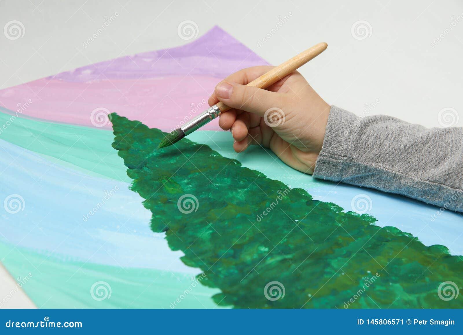 La main de l enfant dessine un arbre de Noël