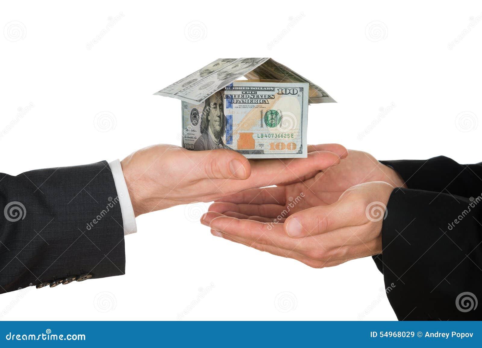 La main de l homme d affaires jugeant la maison faite en dollar américain