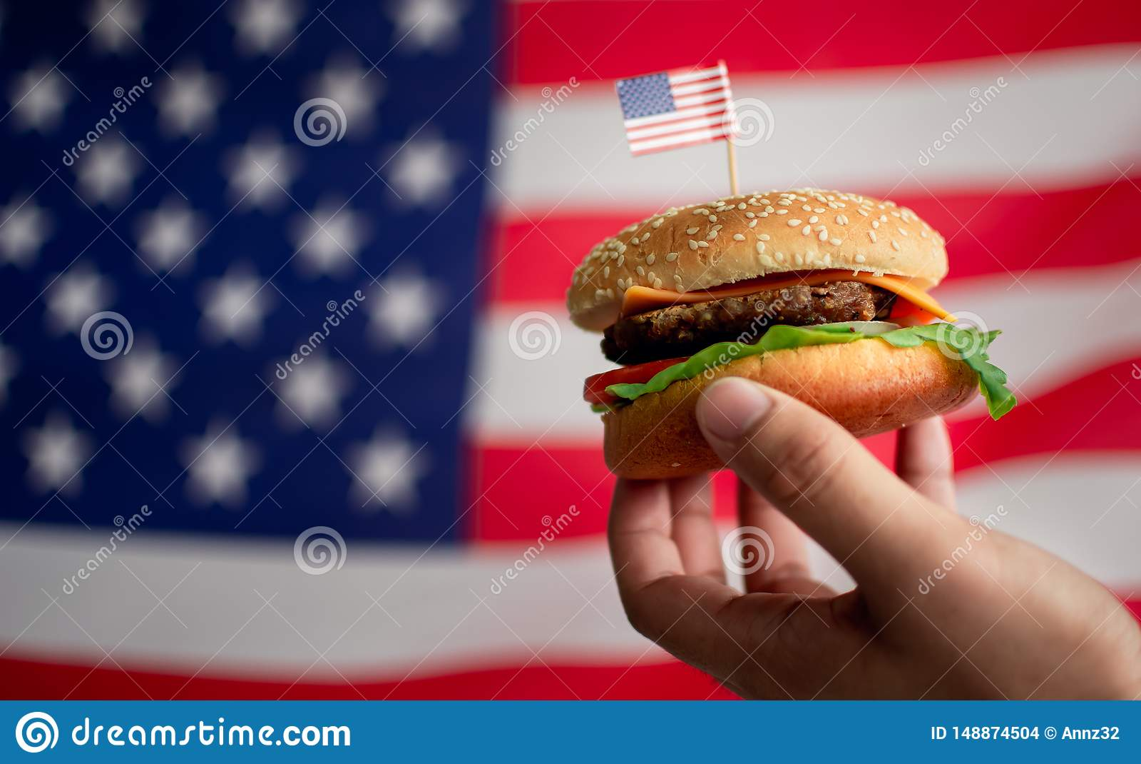 La main de l homme tenant un hamburger avec le fond du drapeau am?ricain