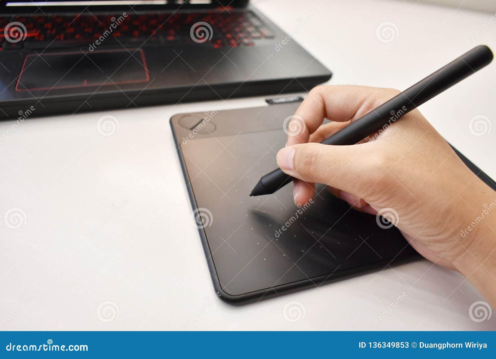 La main de l homme utilisant la souris sans fil de stylo pour le dessin
