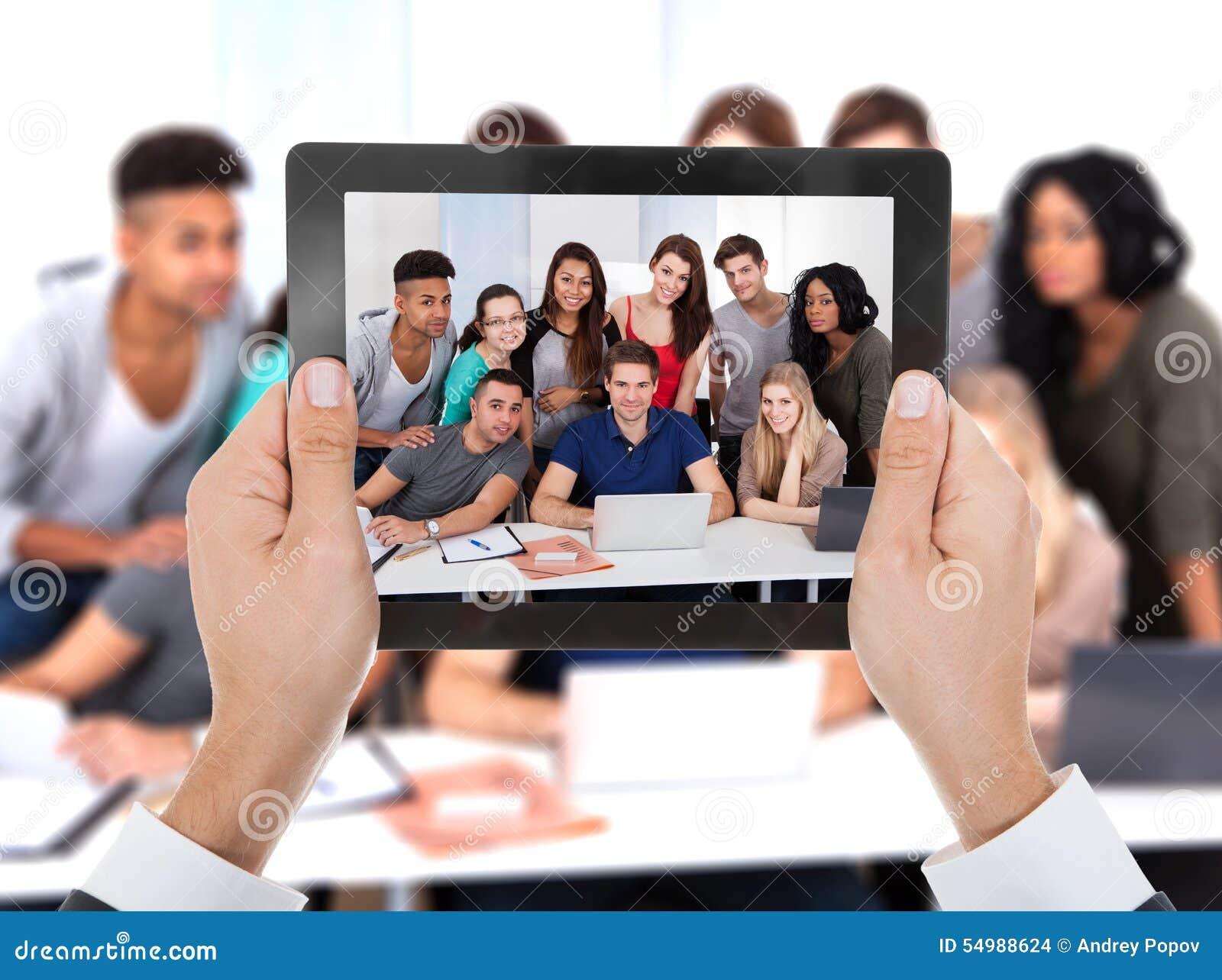La main de personne a photographié le groupe de l étudiant