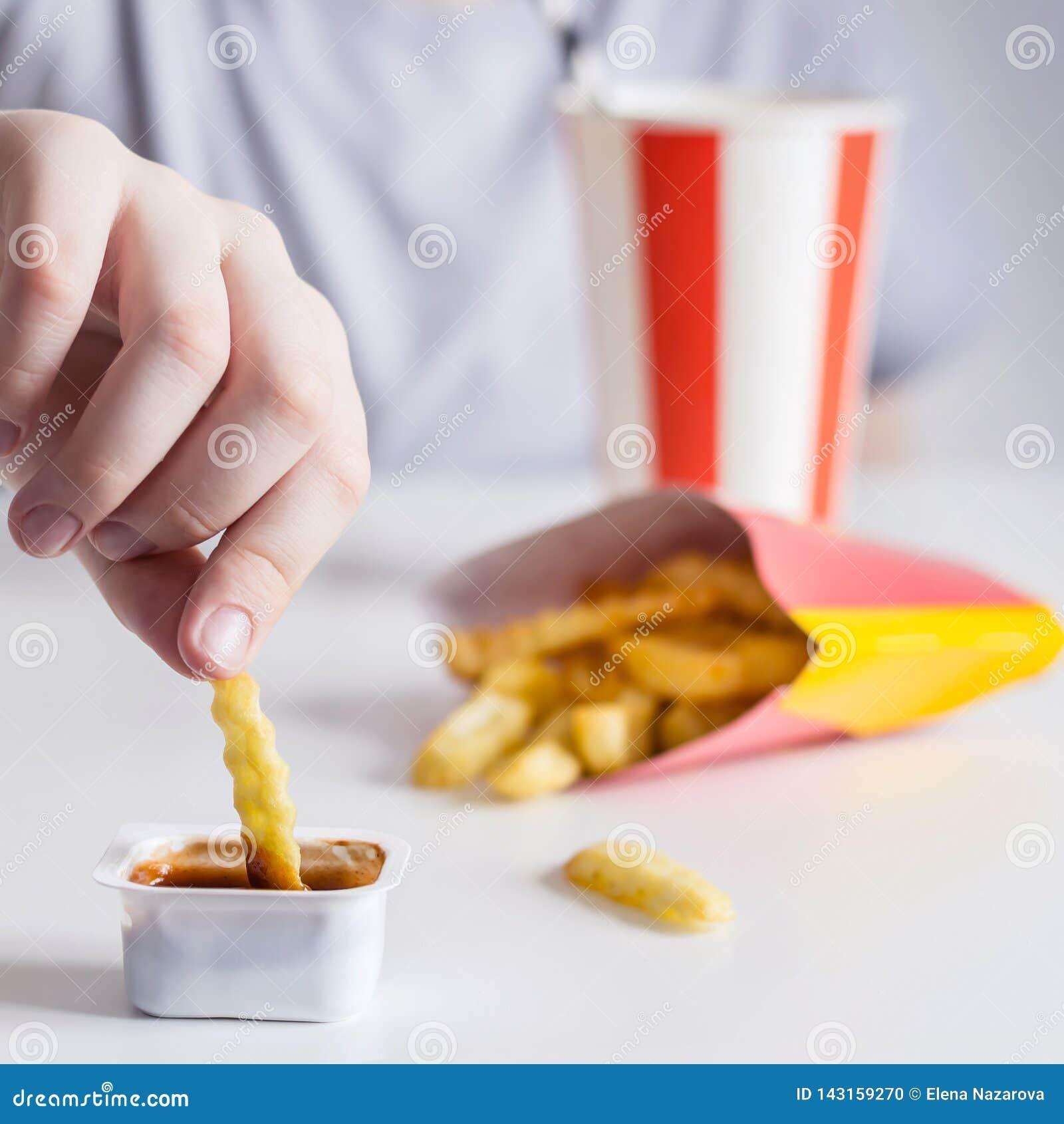 La main des enfants trempe des pommes frites en plan rapproché de sauce, foyer sélectif