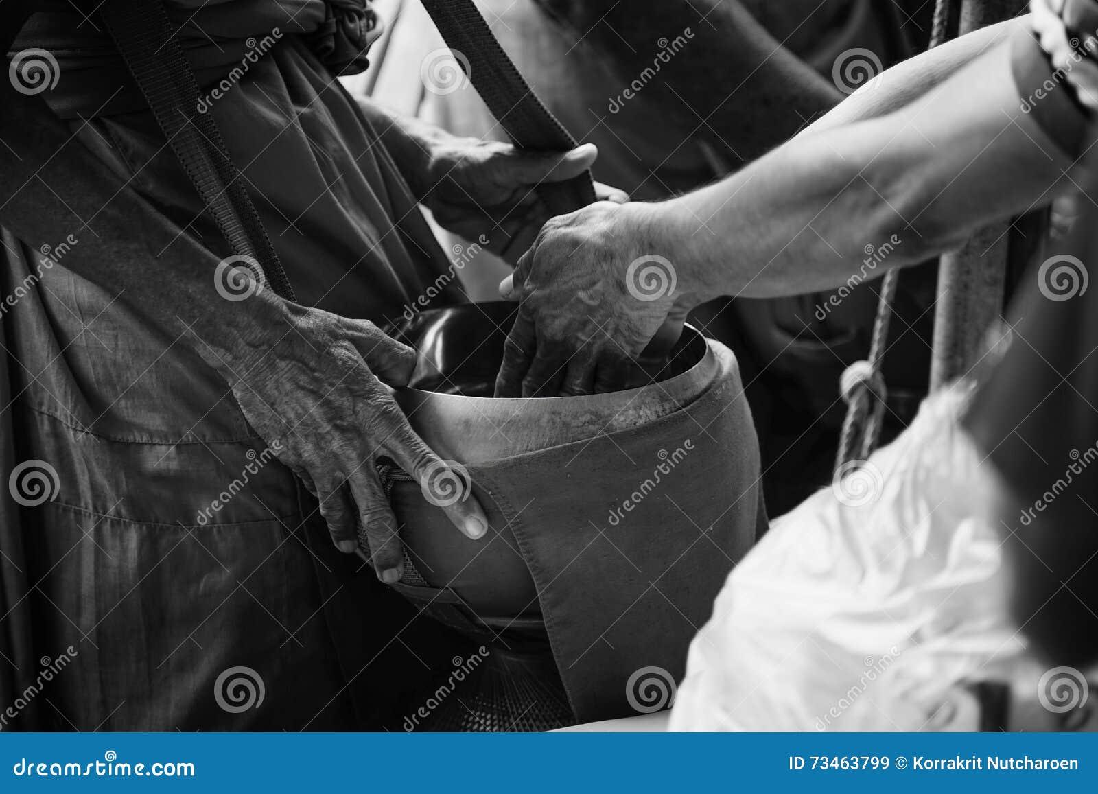 La main deux du bouddhisme de personnes thaïlandaises donnent l aumône au moine dans la cuvette d aumône, style contrasté noir et
