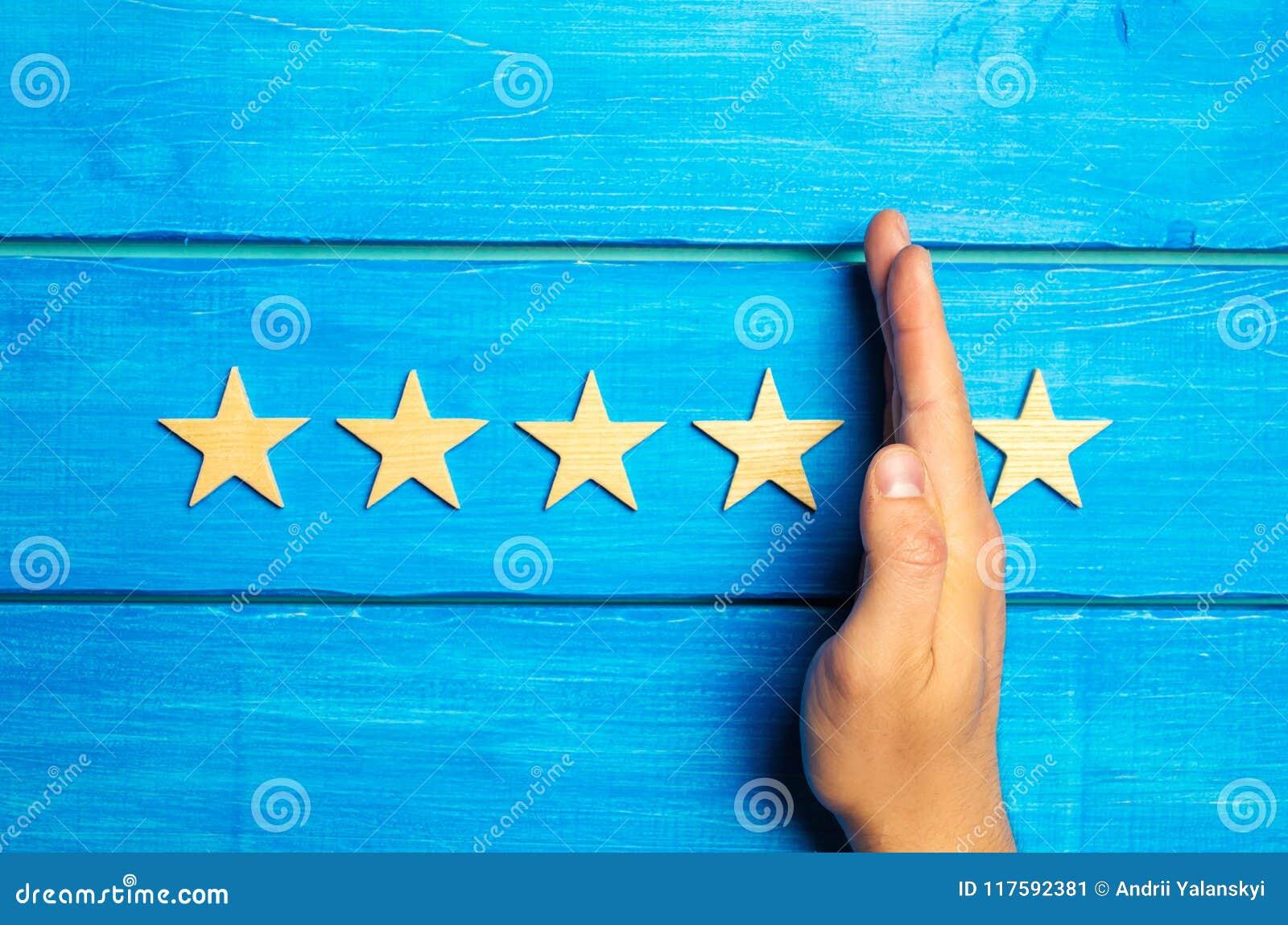 La main divise la cinquième étoile des quatre autres Évaluation de 5 étoiles, 4 étoiles Aperçu de restaurant, hôtel, café