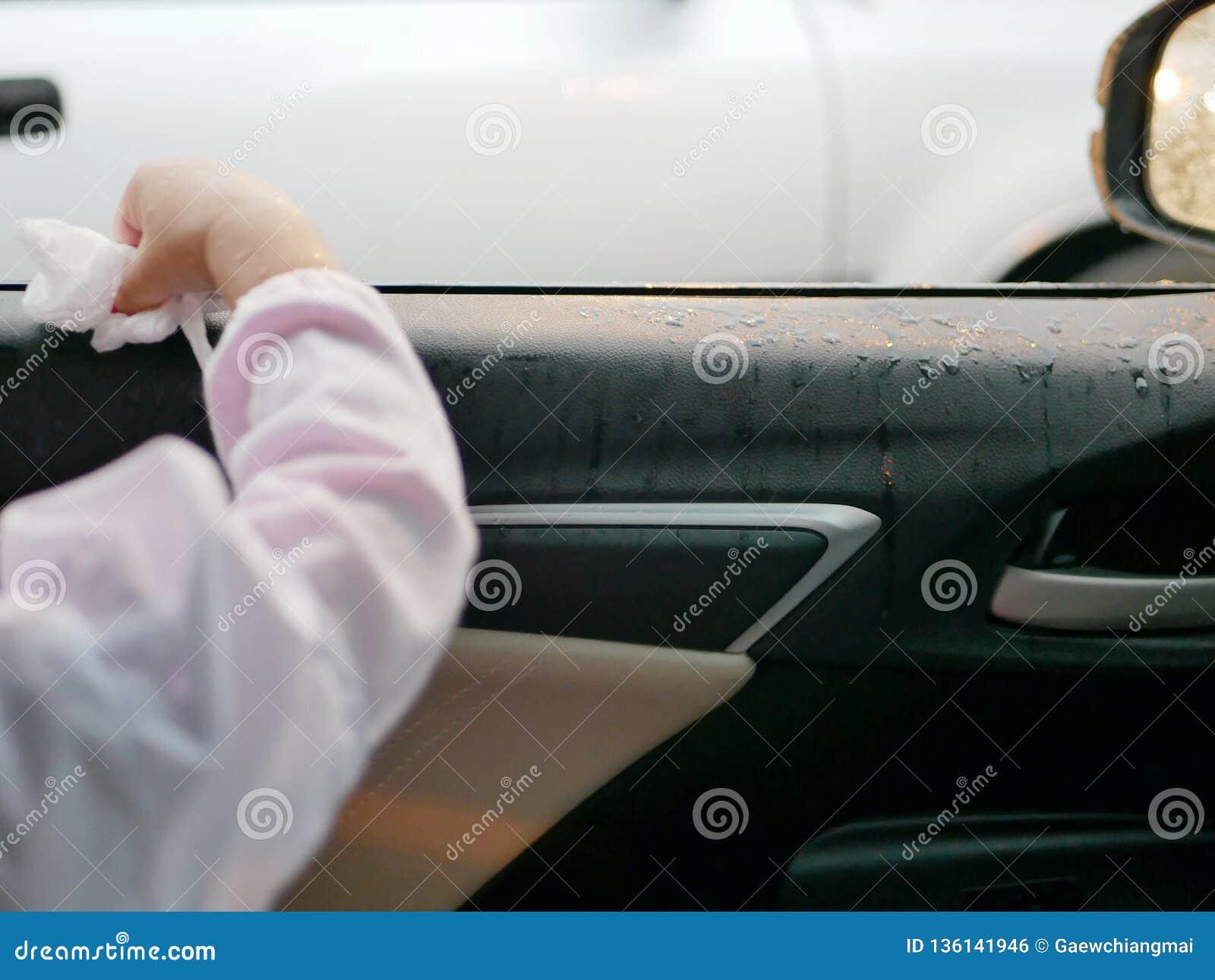 La main du petit bébé essuyant la pluie sur la fenêtre ouverte d une voiture