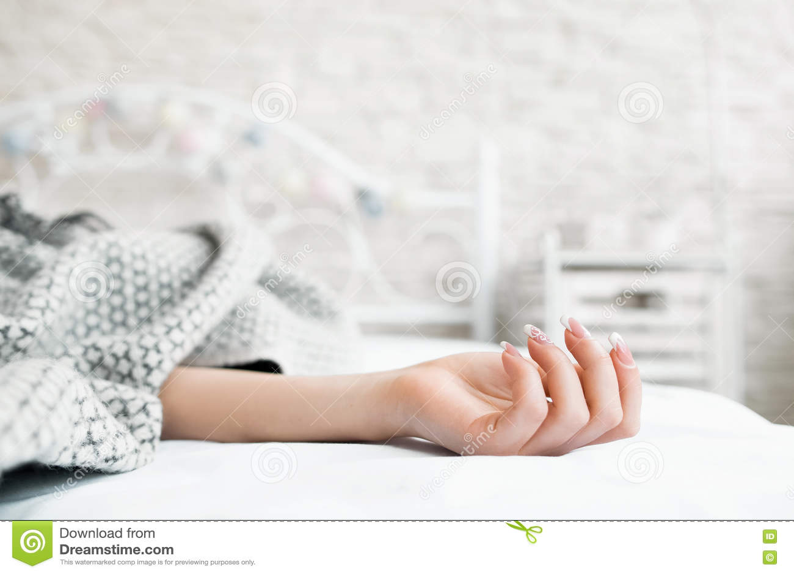 La main du sommeil dans le lit a couvert le plan rapproché de femme