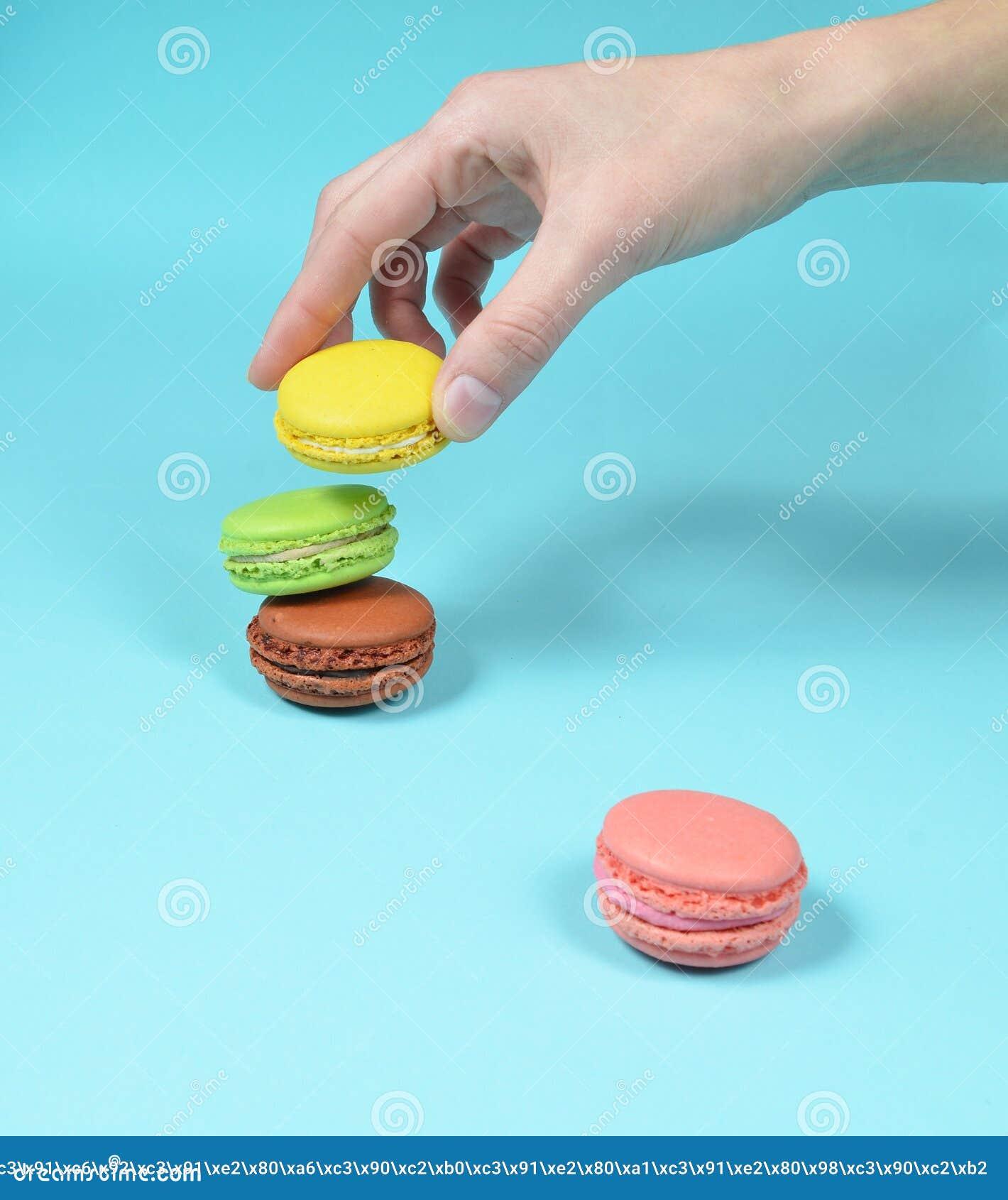 La main femelle abaisse les biscuits jaunes de macarons Une pile de macarons colorés sur un fond en pastel bleu minimalisme
