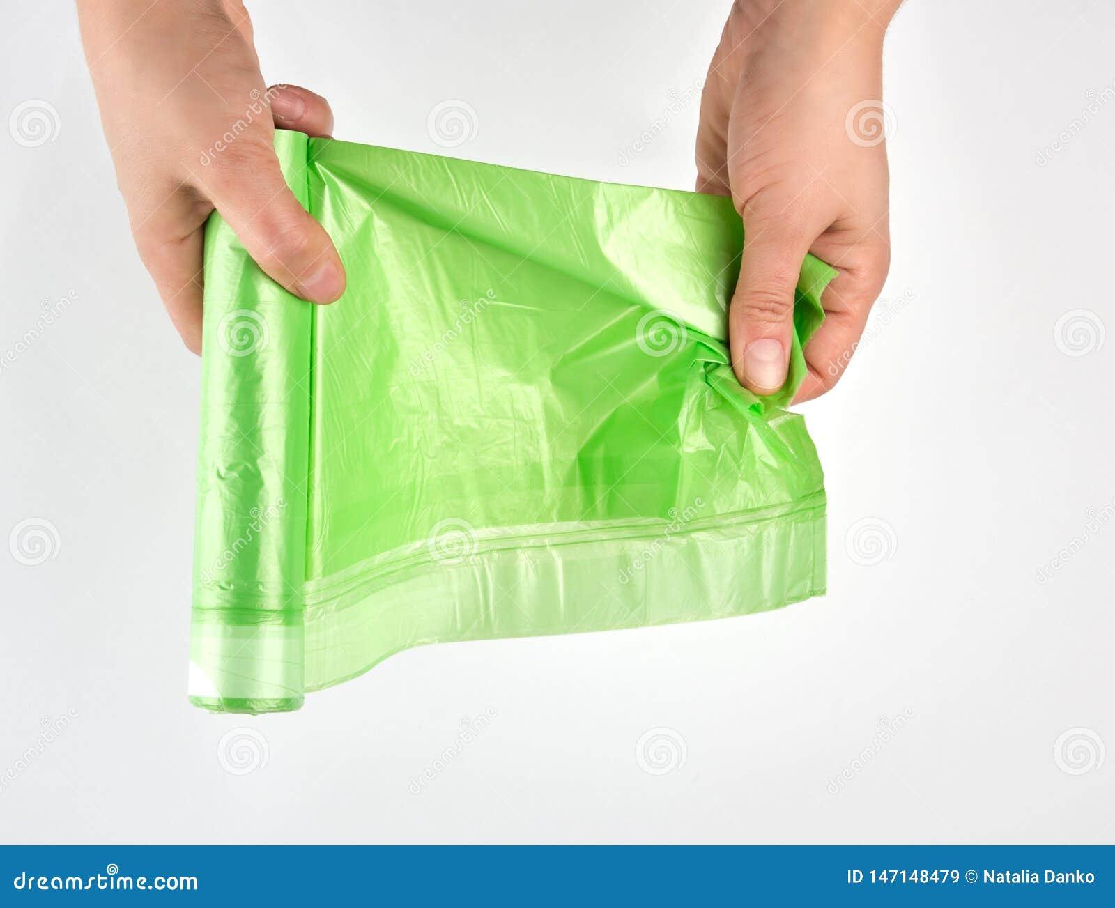 La main femelle d?roulent le petit pain vert avec des sachets en plastique pour des d?chets