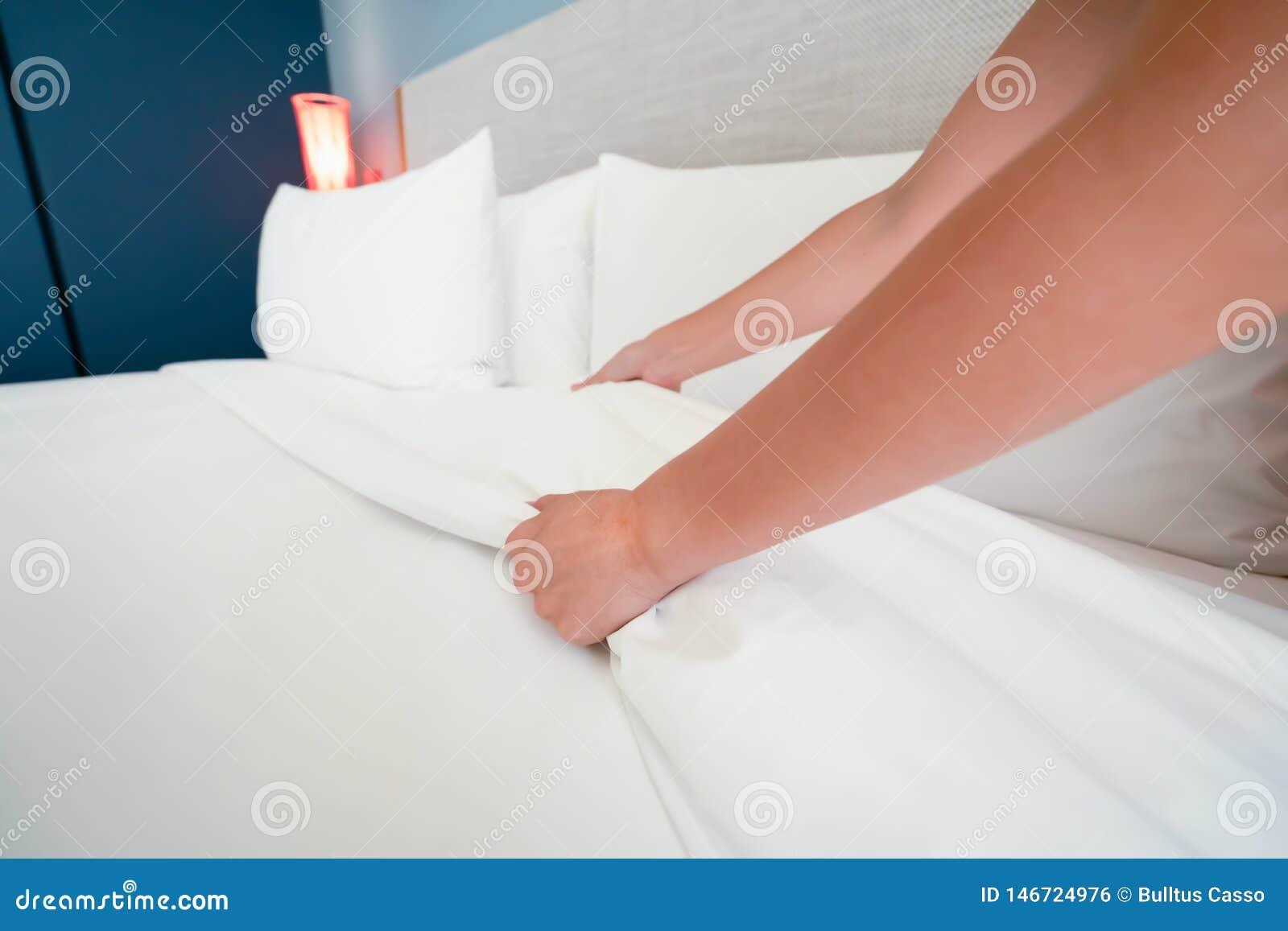 La main femelle a install? le drap blanc dans l h?tel de la chambre