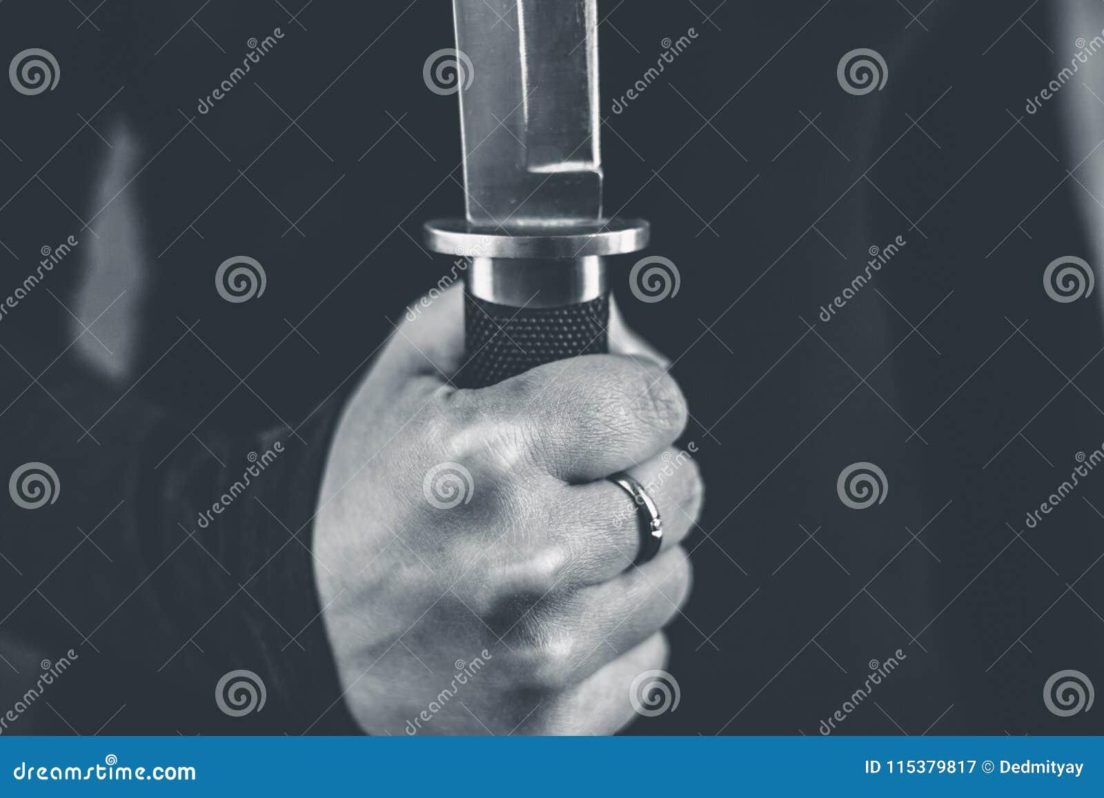 La main femelle tient le concept de couteau, de meurtre et de violence