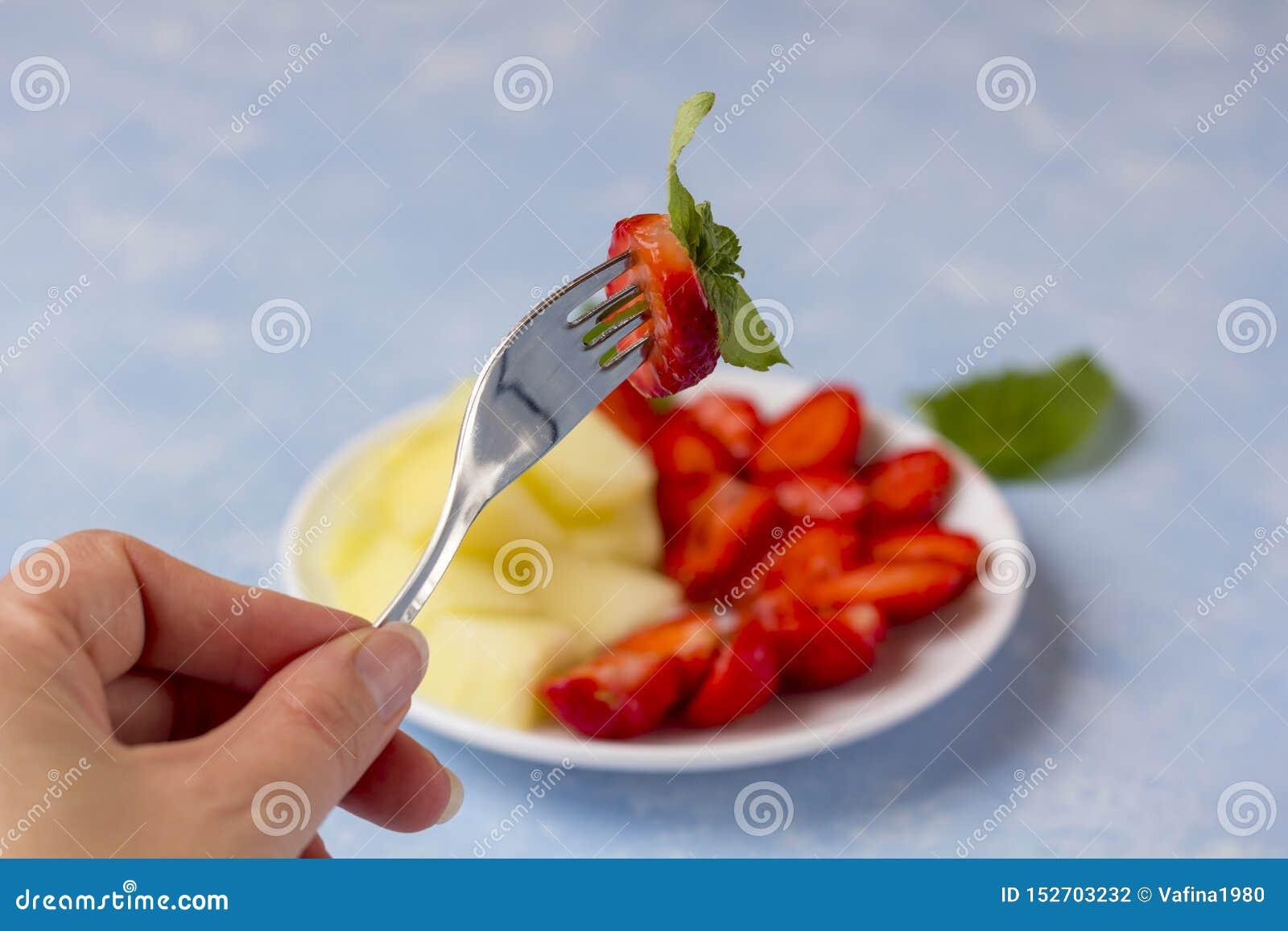 La main femelle tient une baie sur une fourchette Salade de fruits végétarienne organique fraîche