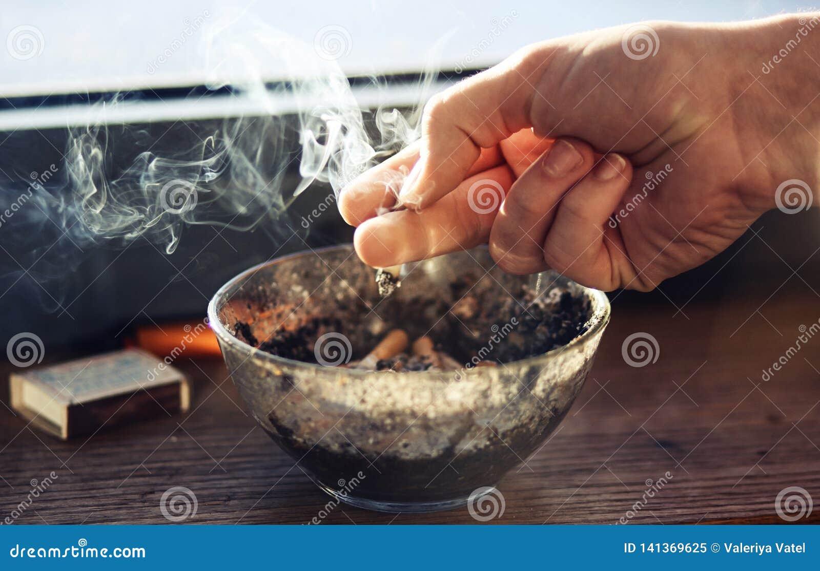 La main humaine se tient au-dessus de la cigarette de cendrier, qui fume fortement