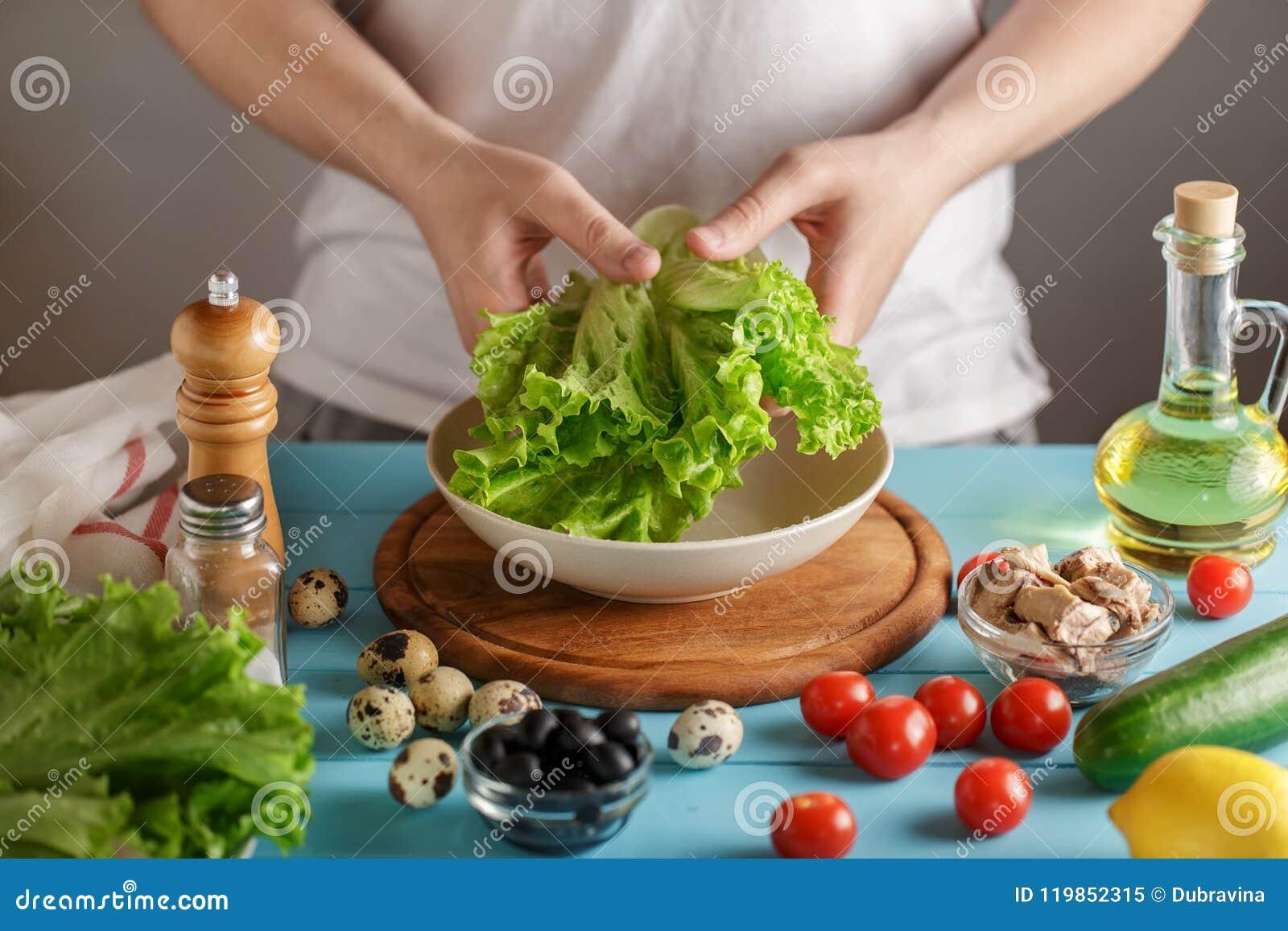 La main masculine tient le groupe de laitue au-dessus de la cuvette sur la table en bois avec les ingrédients frais