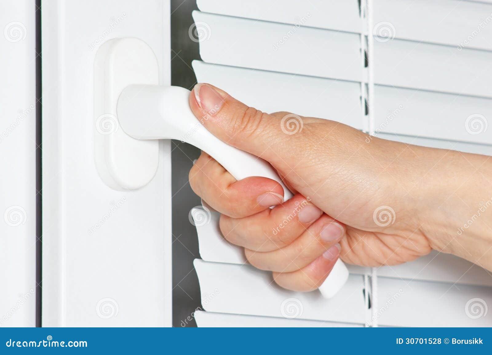 La main ouvre la fen tre en plastique blanche avec la jalousie for Jonas ouvre la fenetre