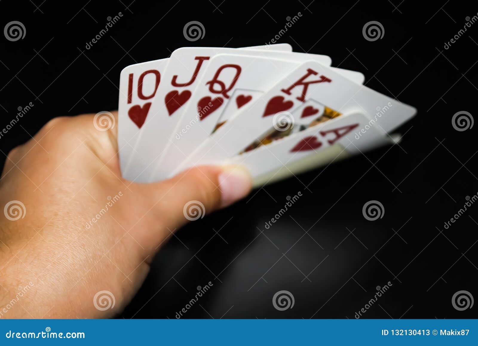 La main tient des cartes sur le fond noir