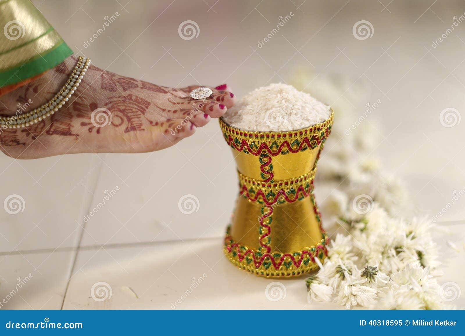 La maison du marié entrant de jeune mariée indoue indienne après l avoir épousé en poussant le pot a rempli du riz avec son pied.