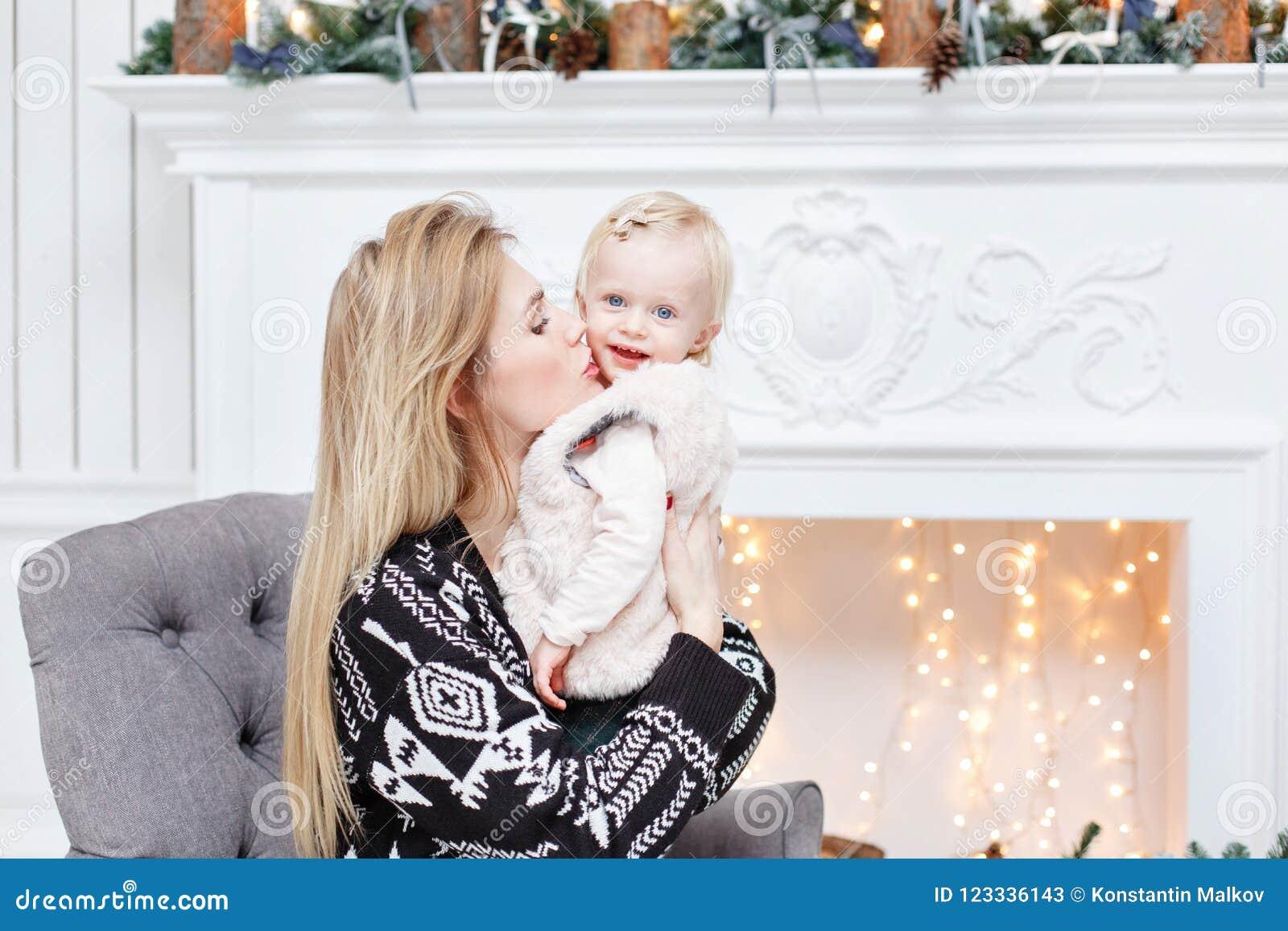 La mamá alegre abraza a su hija linda del bebé Padre y pequeño niño que se divierten cerca del árbol de navidad dentro loving