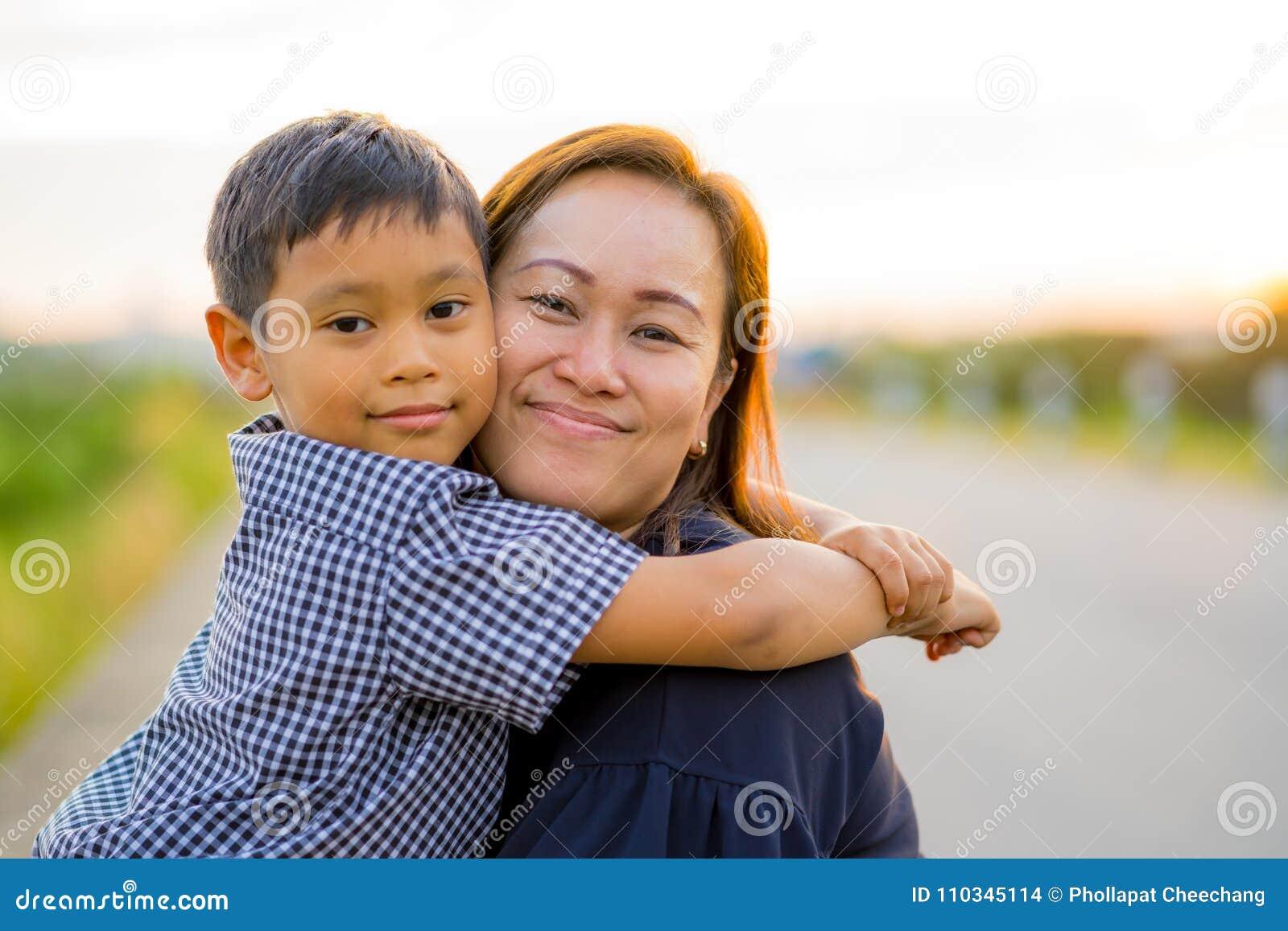 La mamá asiática abraza a su hijo joven cariñosamente en la puesta del sol con el backg de la naturaleza