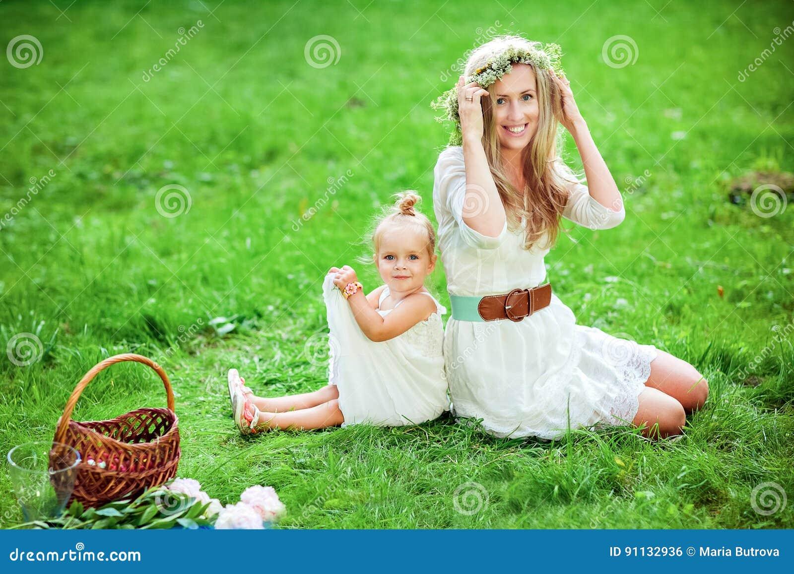 La mamá con una guirnalda en su cabeza y la hija se están sentando en GR