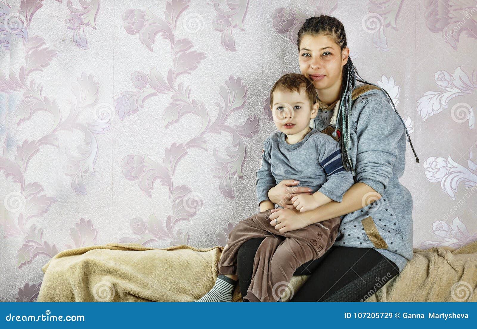 La mamá joven del negro o de Latina y su pequeño hijo se están sentando en el sofá en casa Concepto: Día del ` s de la madre, fam