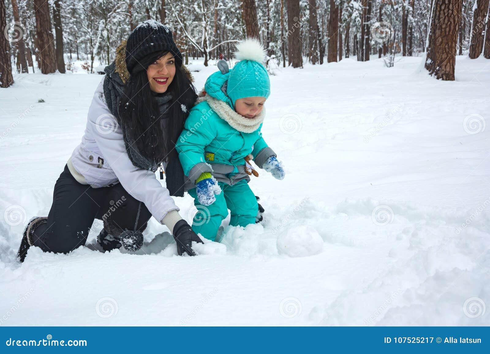 La mamá juega con el niño en la nieve