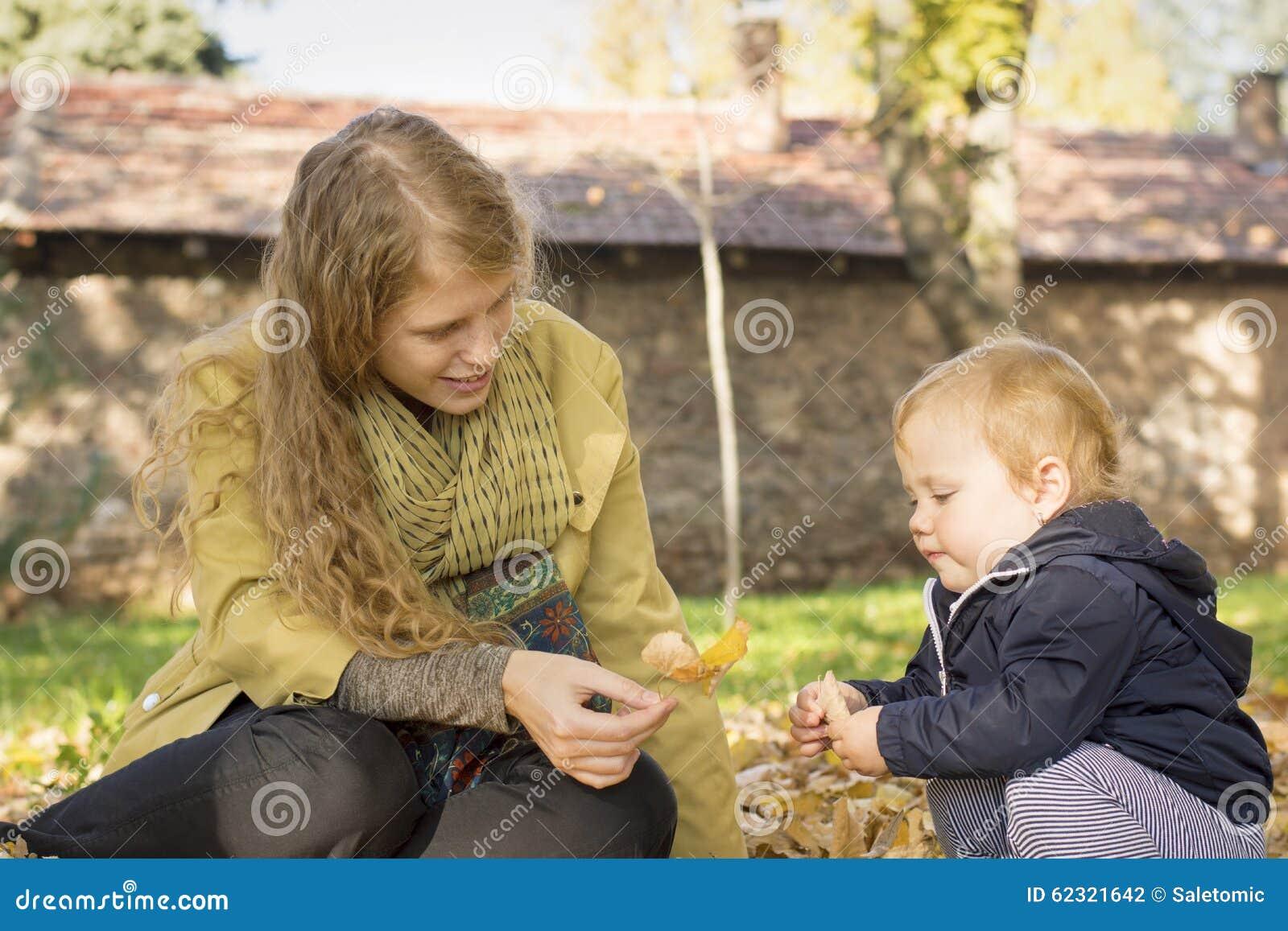 La mamá rubia juega con su hija dulce en el parque