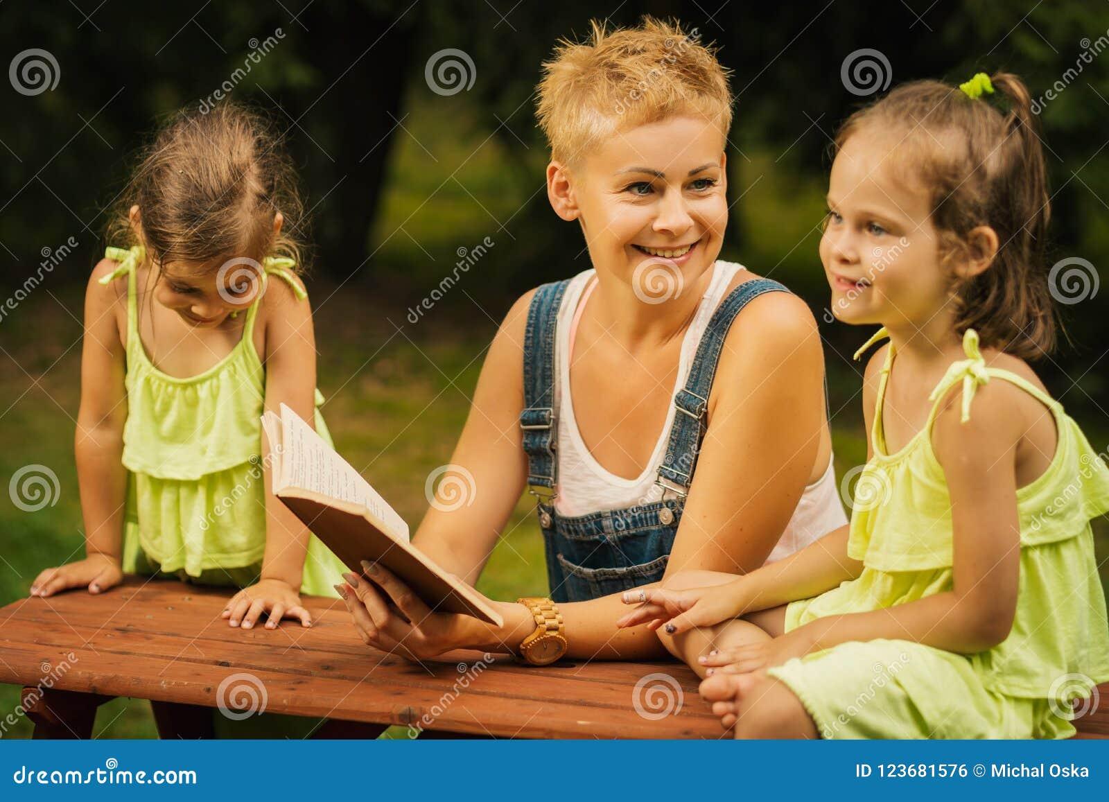 La mamá y dos hijas adorables hablan el uno al otro en el bosque del verano