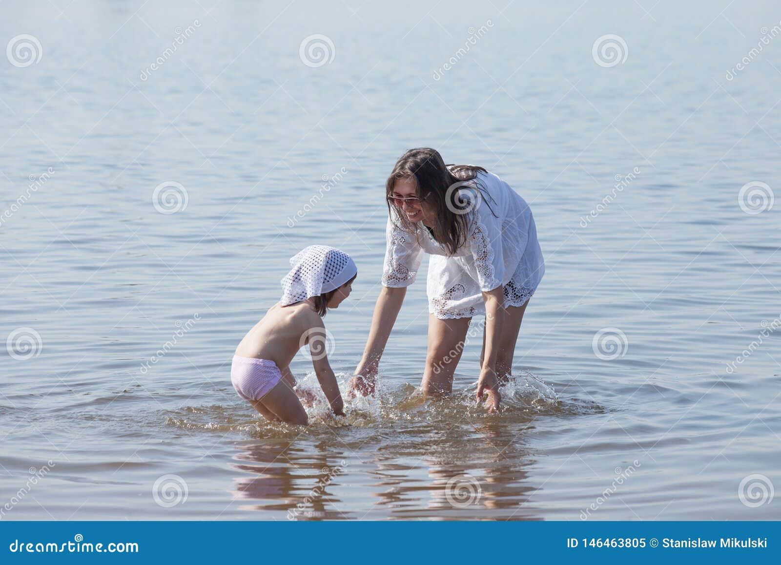 La mamá y la hija están jugando en el río