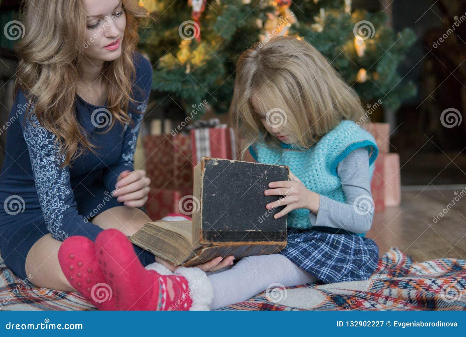 La mamá y la hija pasan el tiempo libre que leen un libro en el árbol de navidad