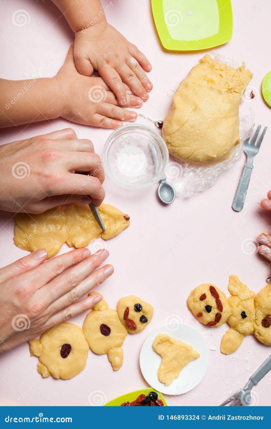 La mamá y la hija se están preparando para la Navidad, cocinan las galletas festivas Muñecos de nieve y árboles de navidad