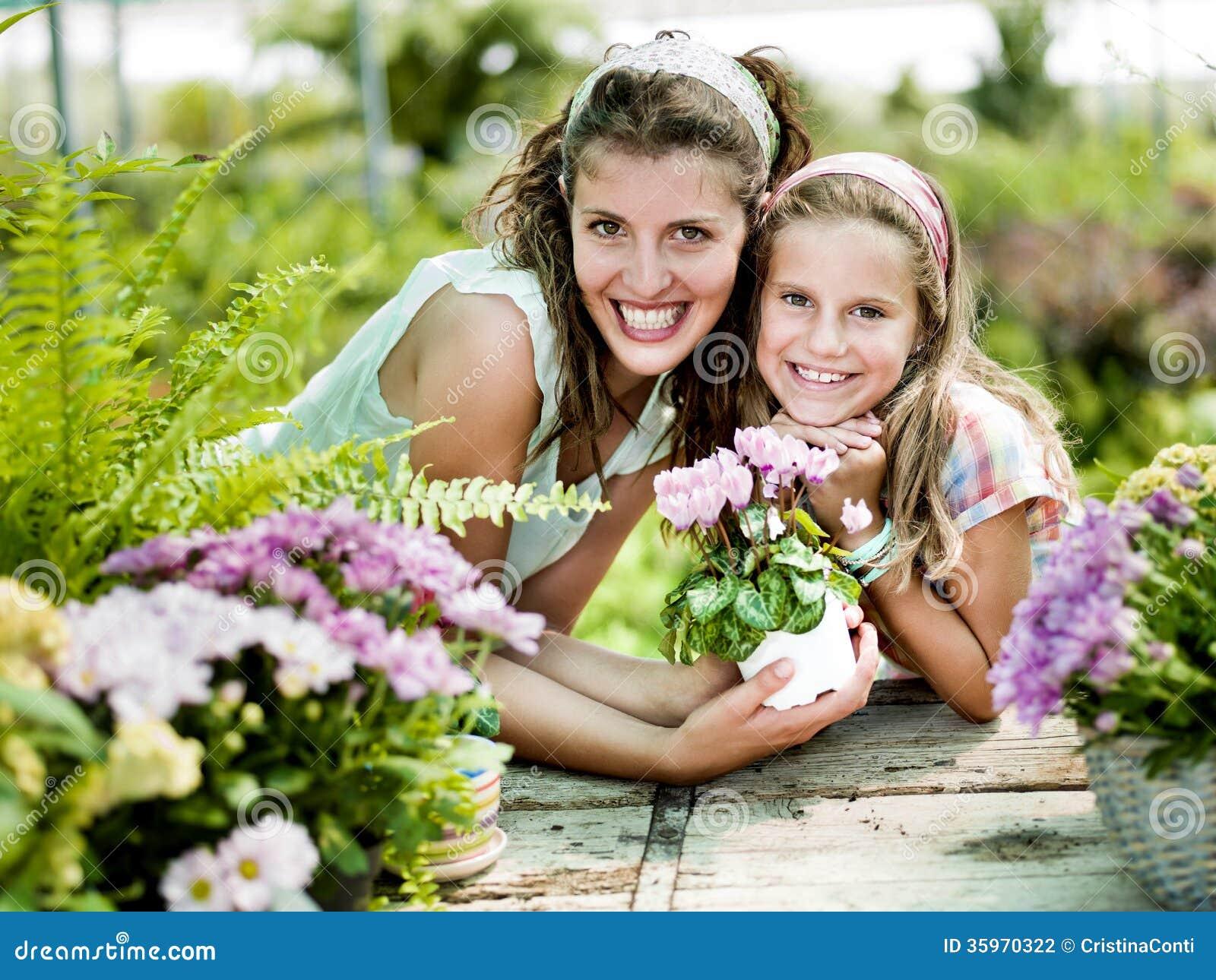 La mamá y la hija se divierten en el trabajo de cultivar un huerto