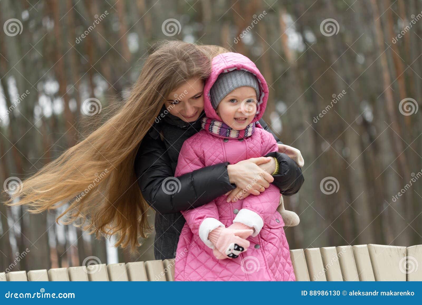 La mamá y la hija se están sentando en un banco de parque