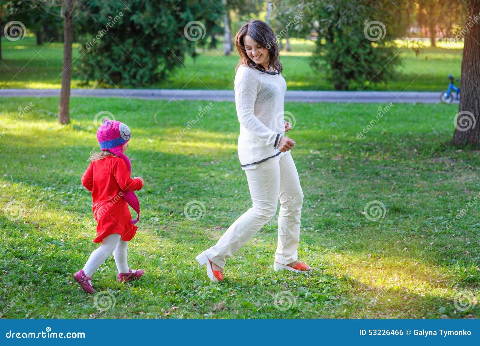 La mamá y la pequeña hija que caminan en el verano parquean