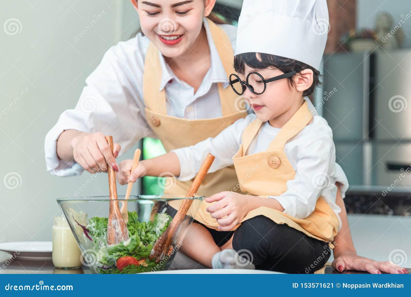 La mamá y su pequeña hija que cocinan la salsa boloñesa para la ensalada en la cocina, allí es vapor que se escapa de la cacerola