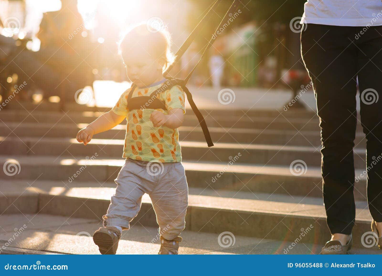 La maman assure son enfant pendant une promenade