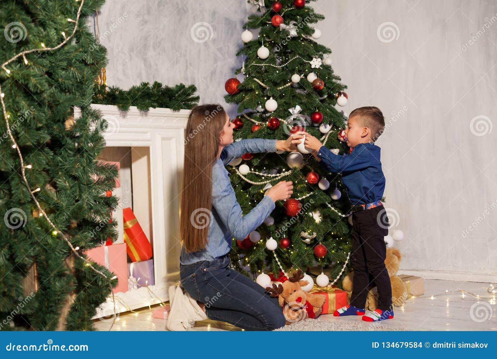La maman avec le fils orner l arbre de Noël allume la nouvelle année de Noël