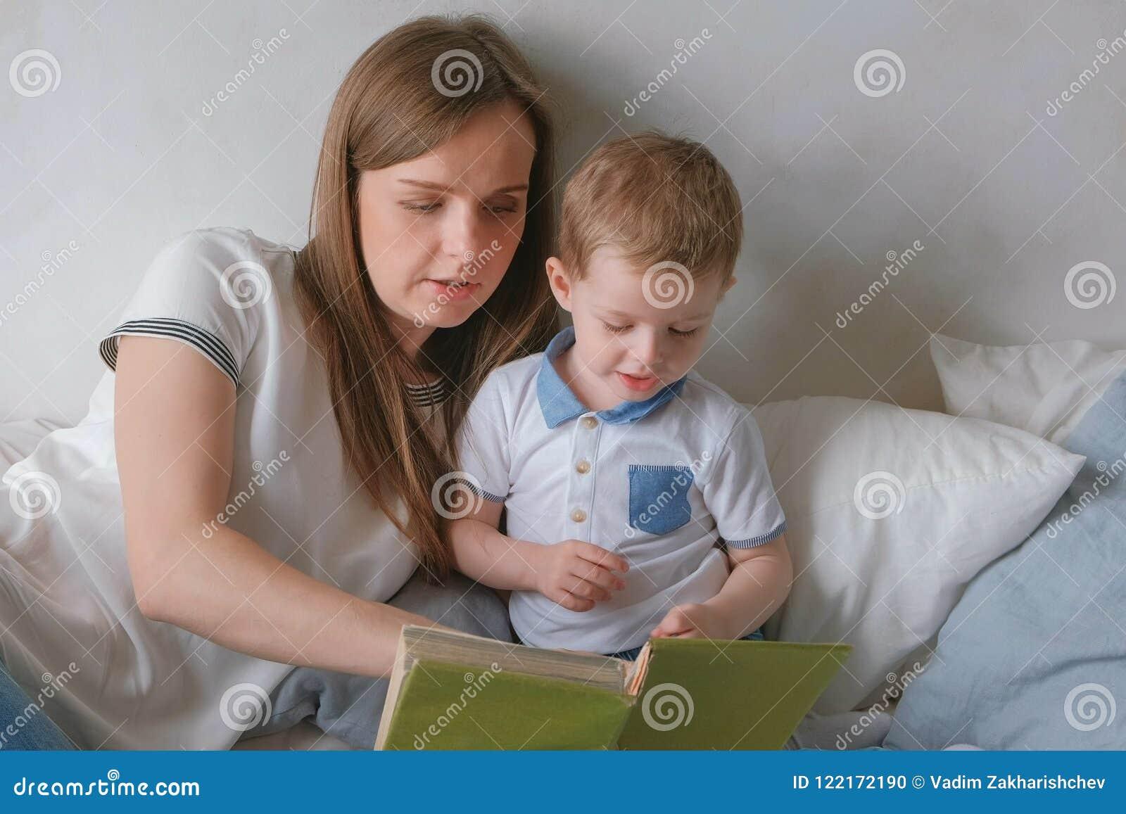 La maman de famille et l enfant en bas âge de fils ont lu des livres s étendant sur le lit Temps de lecture de famille