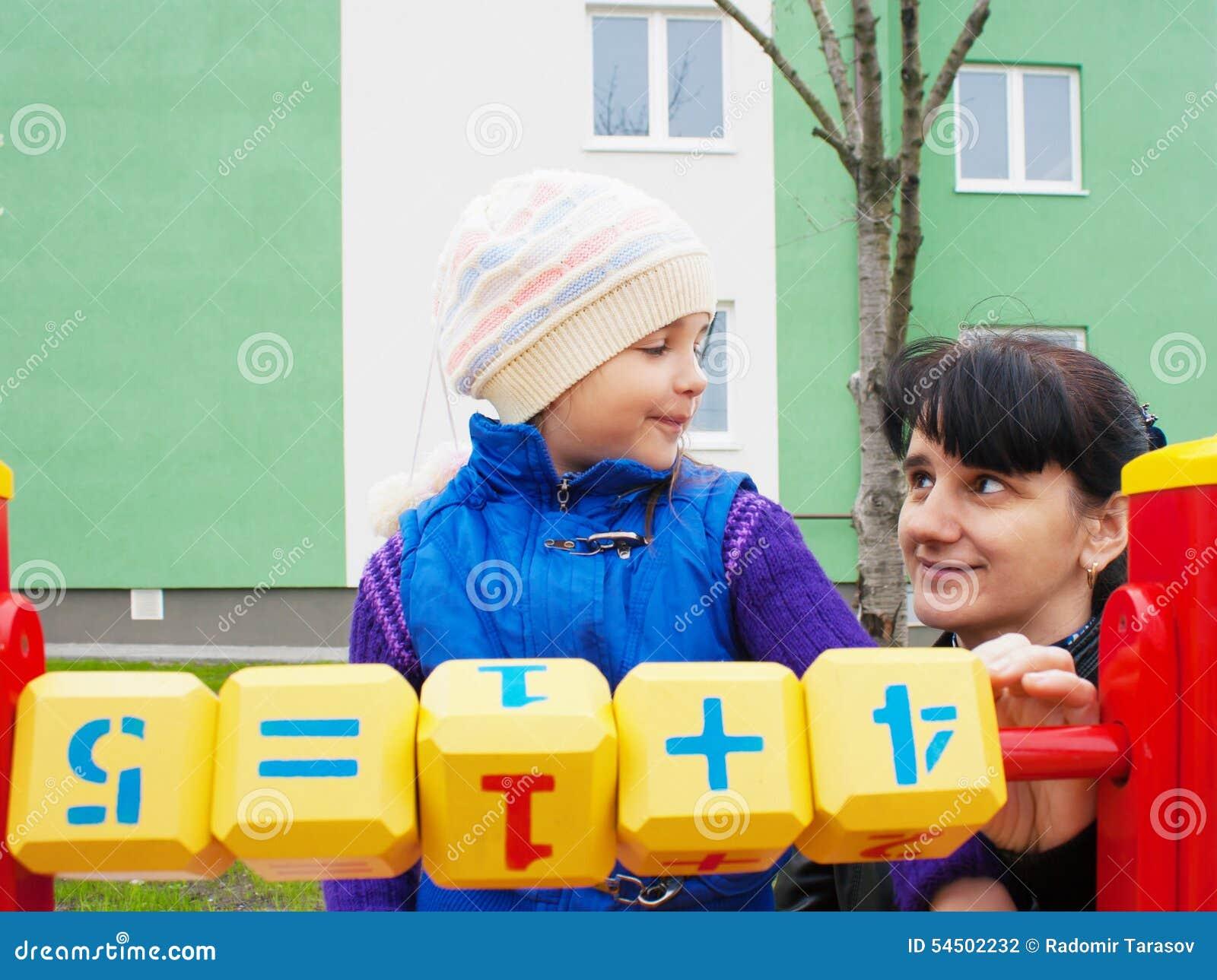 La maman enseigne la fille à être considérée avec les cubes en bois