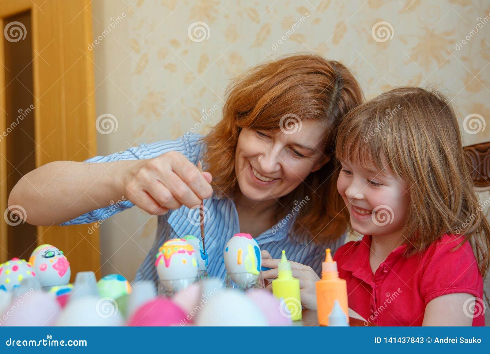La maman et la fille prennent les oeufs de peinture d amusement pour Pâques