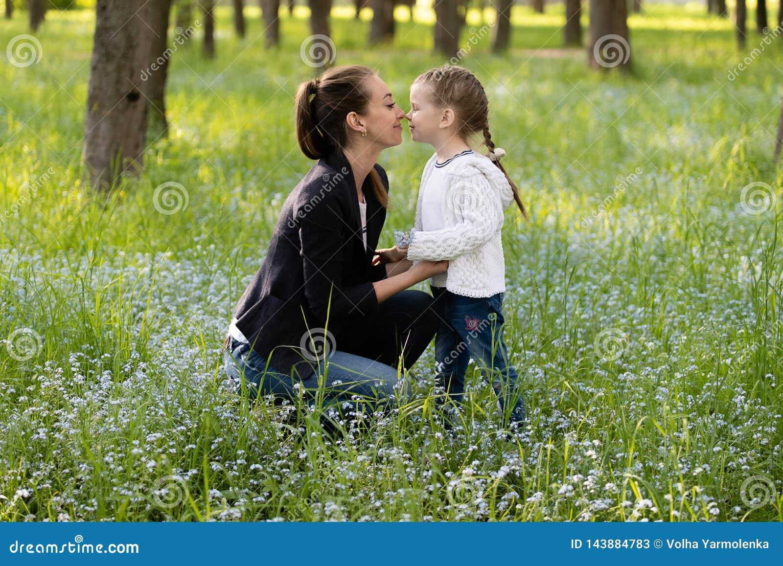 La mamma accovacciata e tocca delicatamente il naso della figlia