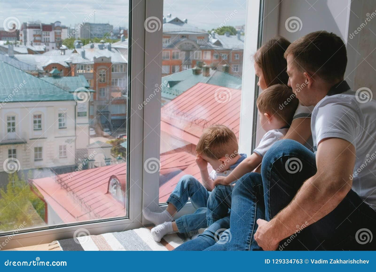 La mamma della famiglia, il papà e due bambini dei fratelli gemelli esaminano fuori la finestra la città