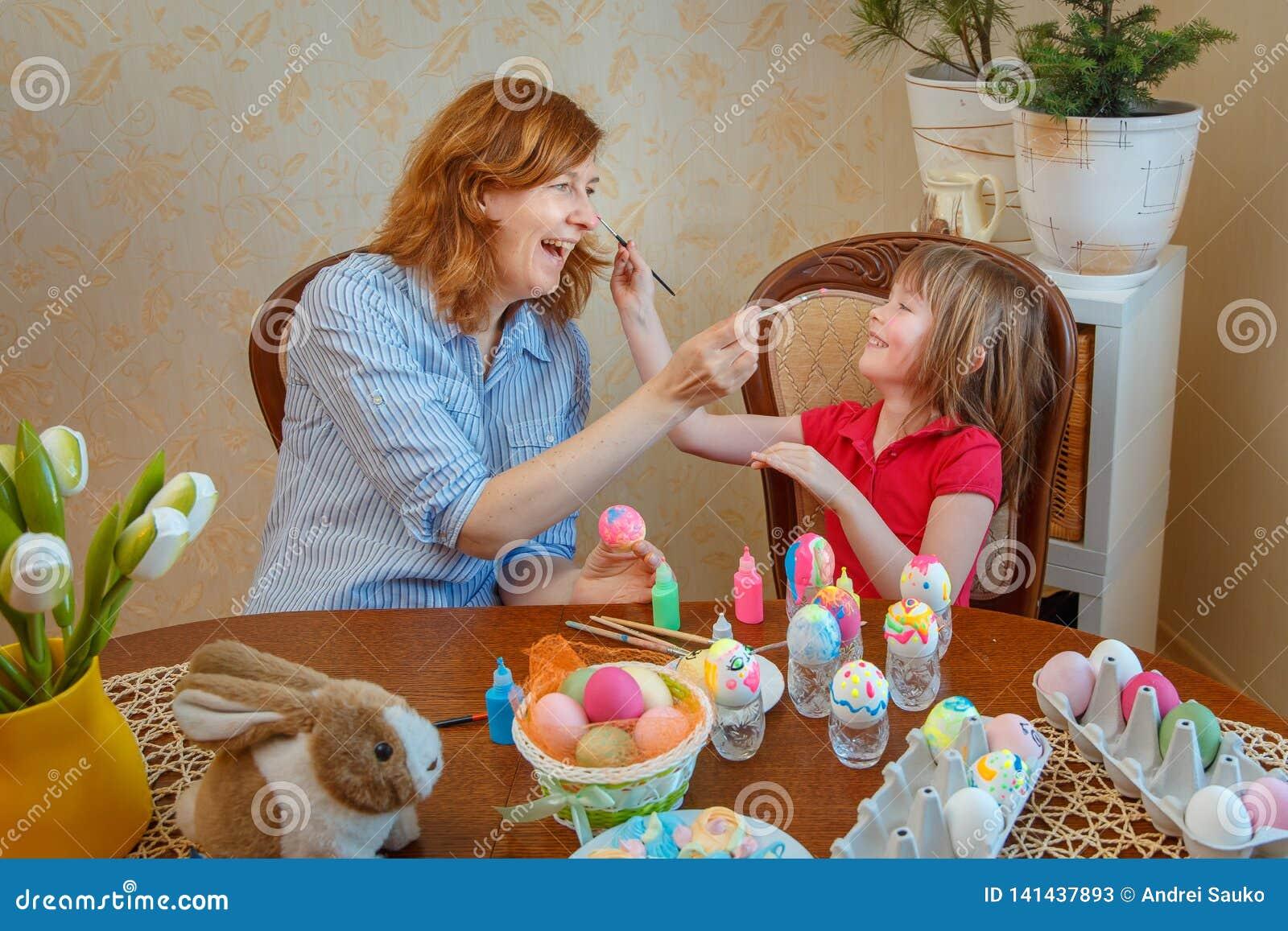 La mamma e la figlia si divertono le uova della pittura per Pasqua