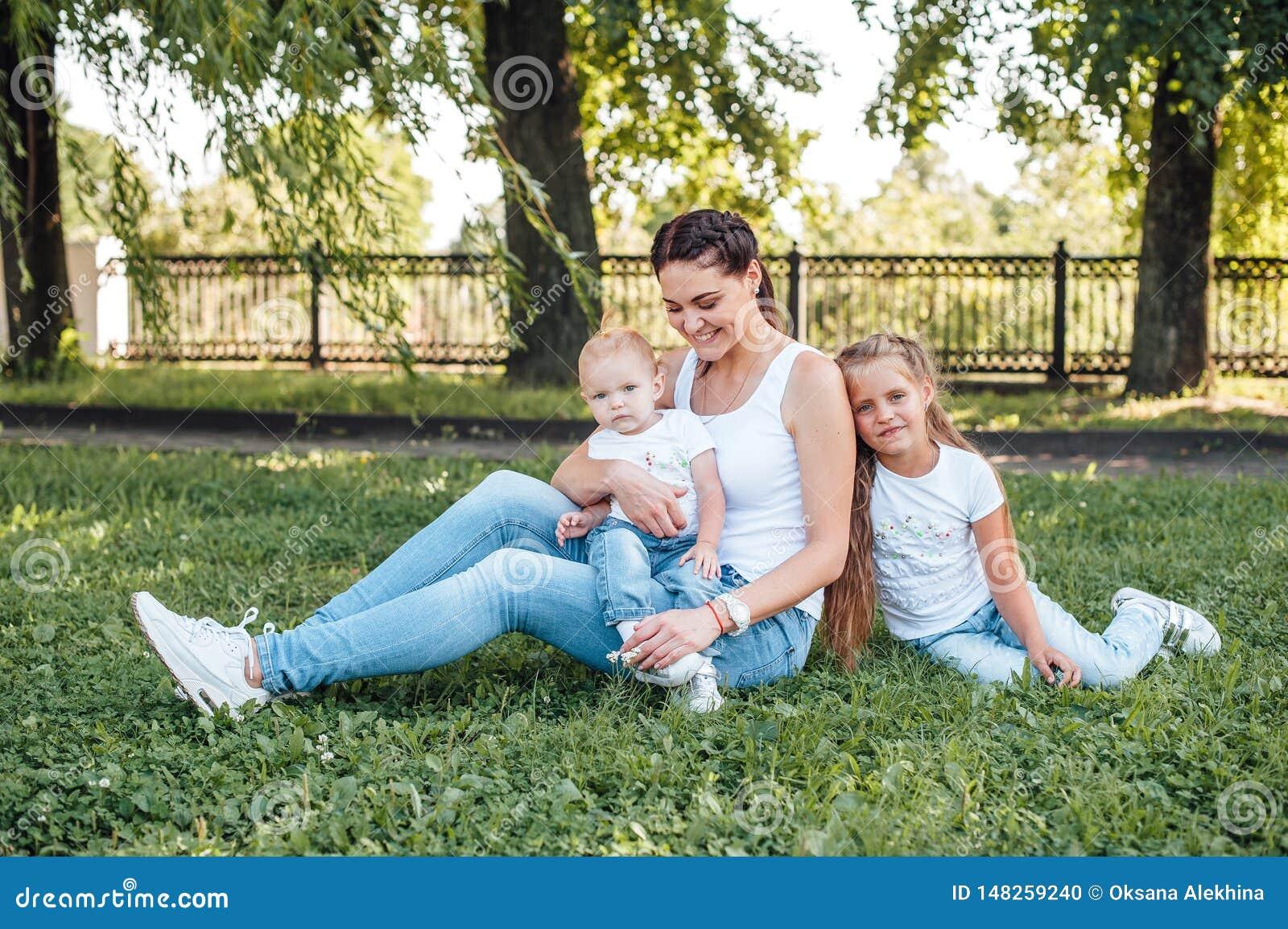 La mamma e le sue figlie stanno camminando nel parco dell estate